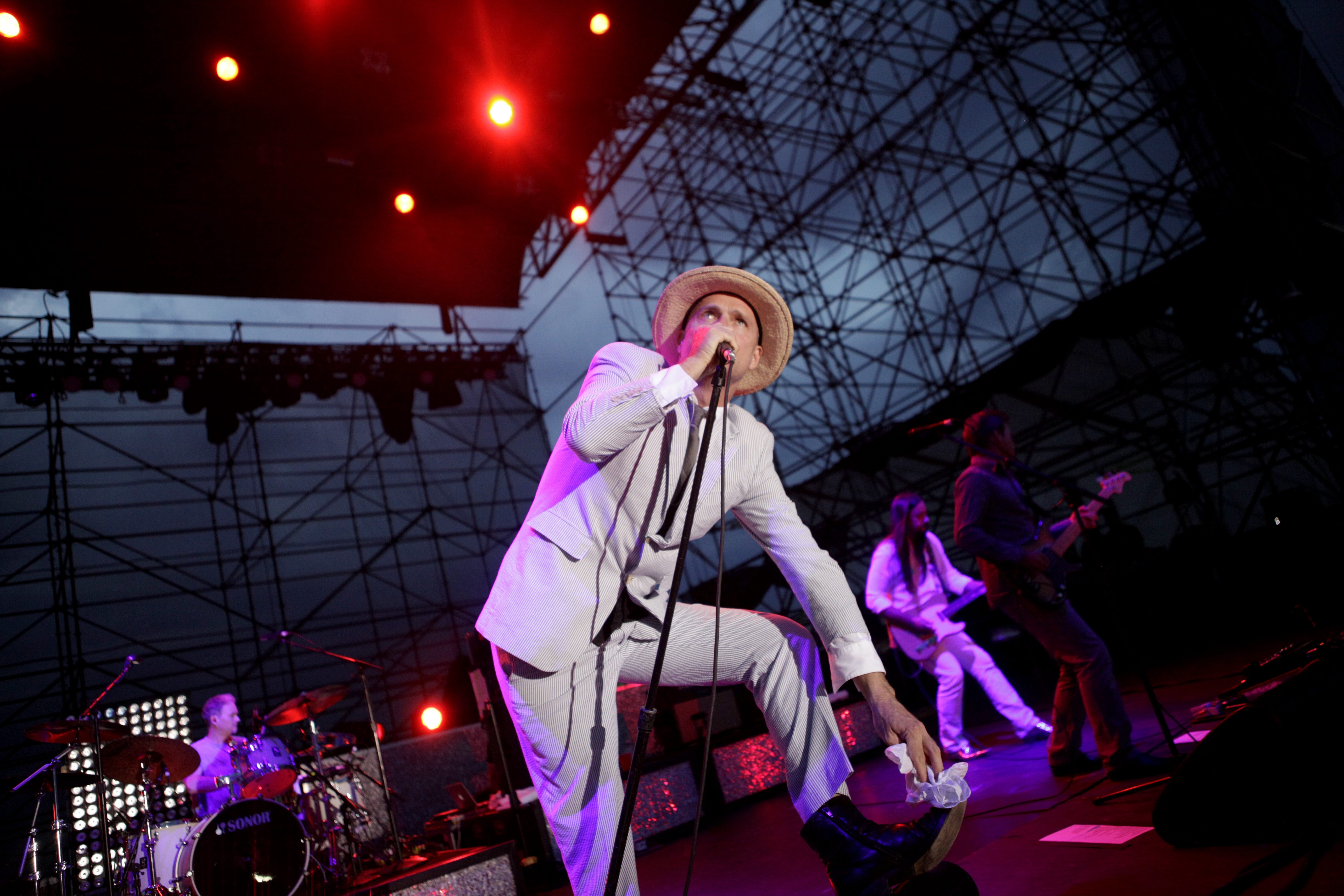 Lead singer Gord Downie, dressed in a seersucker suit with a black tie and fedora, performs with the Tragically Hip at Friday night's brief concert at the Outer Harbor.