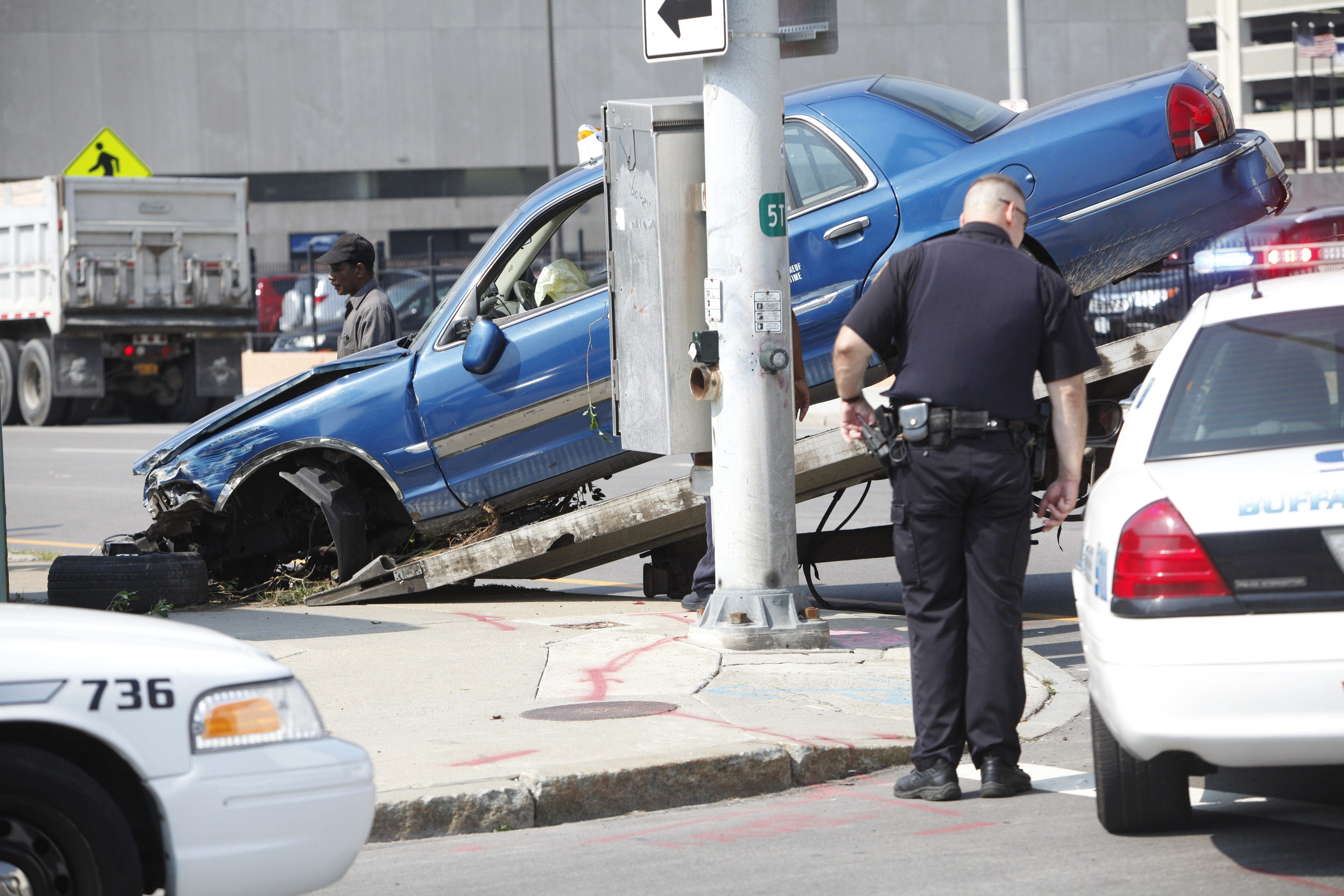 One of the vehicles involved in a crash at the intersection of Clinton and Oak streets Friday is loaded onto a flatbed truck. Six people were injured when a taxi hit another car then crashed into the Heritage Centers building on the corner.