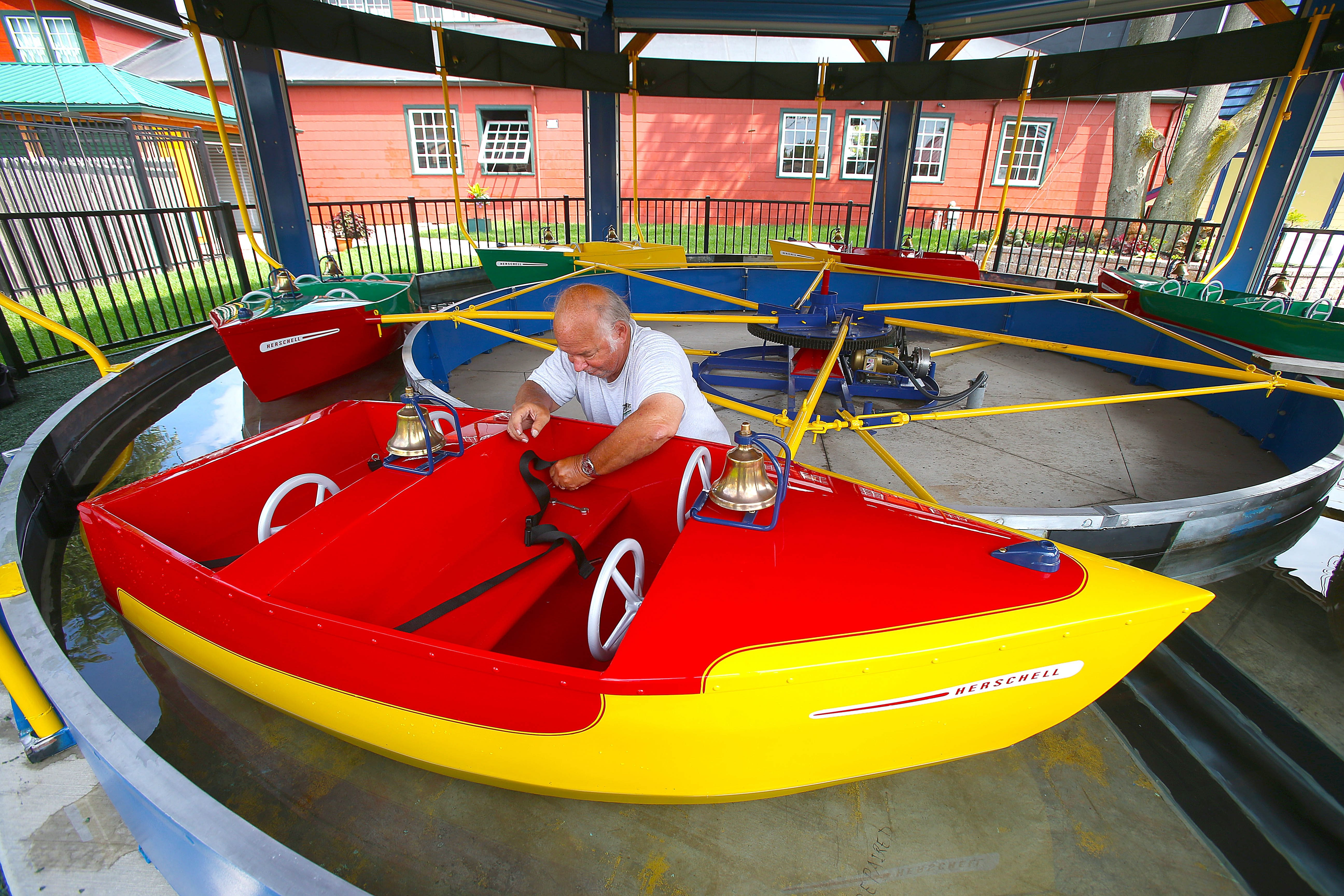 """Herschell Carrousel Museum volunteer Ron Witt attaches safety belts to the refurbished 1957 Wet Boat Ride  at the new """"Kiddieland Testing Park"""" at the North Tonawanda museum on Wednesday. The park opens Saturday to the public.   Robert Kirkham/Buffalo News"""
