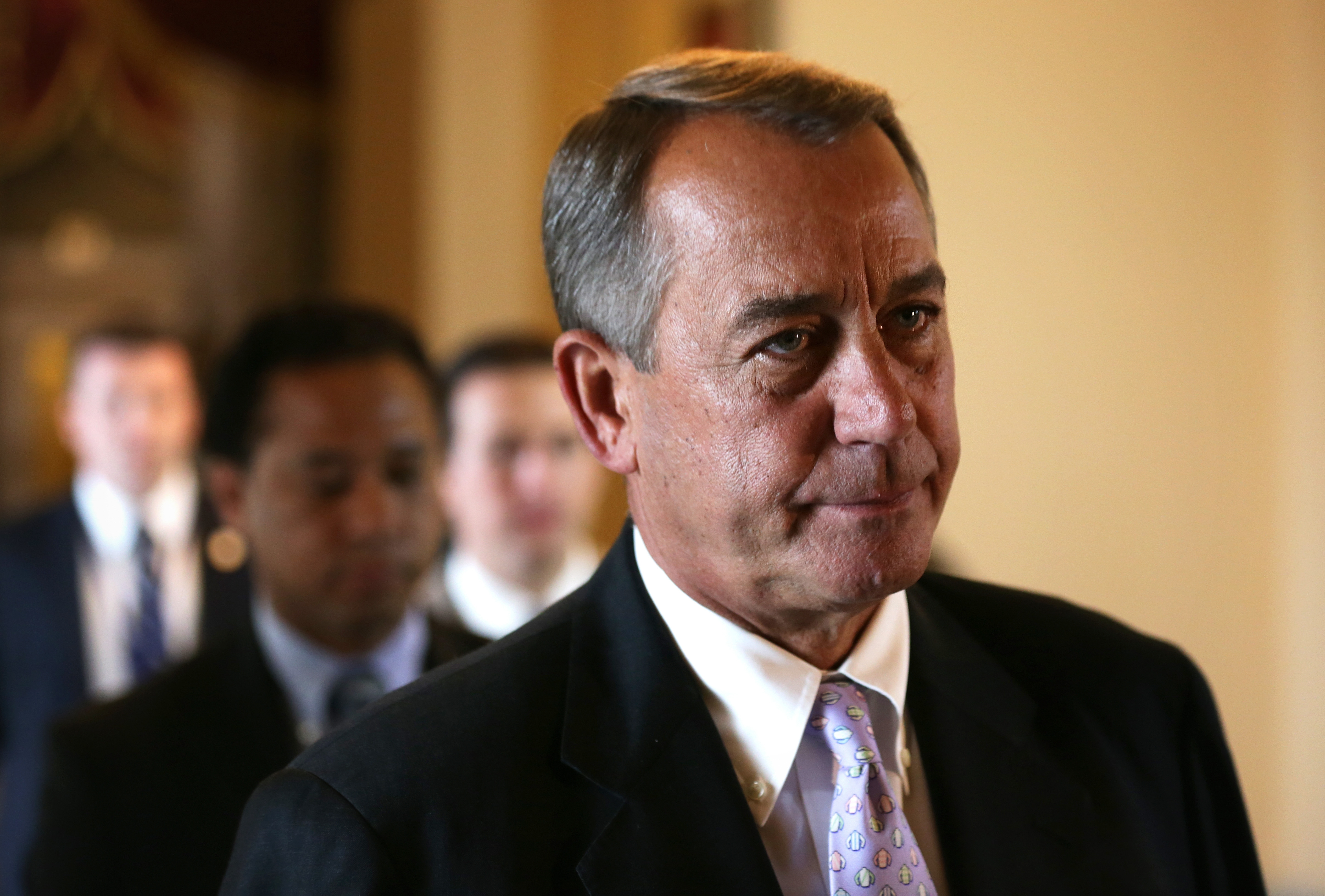Speaker John Boehner heads to the House chamber for a procedural vote Saturday on a bill to link health care and the budget.