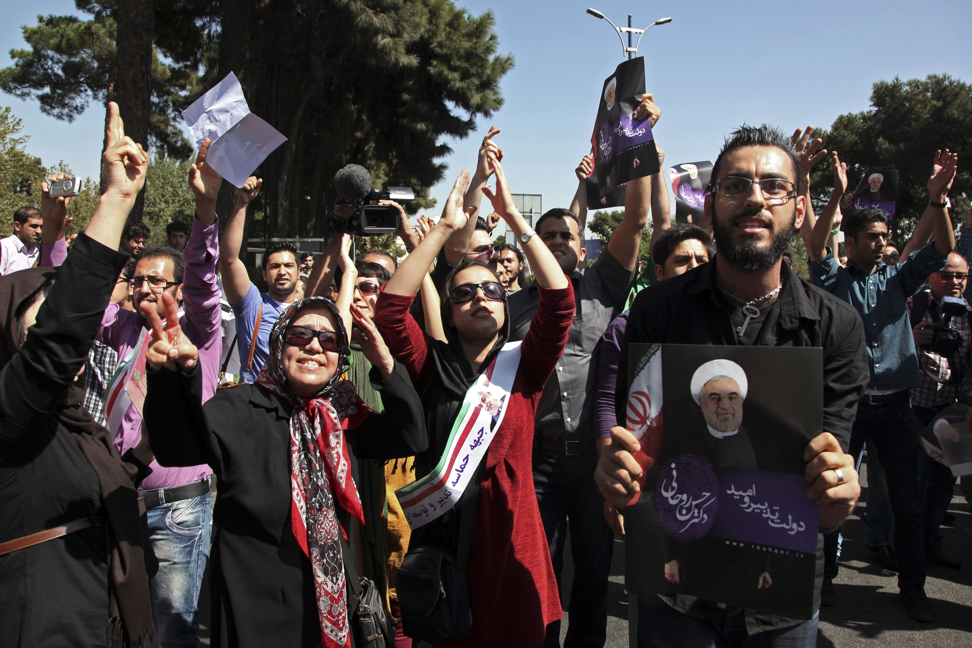 Supporters of Iranian President Hassan Rouhani cheer his arrival in Tehran on Saturday after his unexpected phone conversation with President Obama.