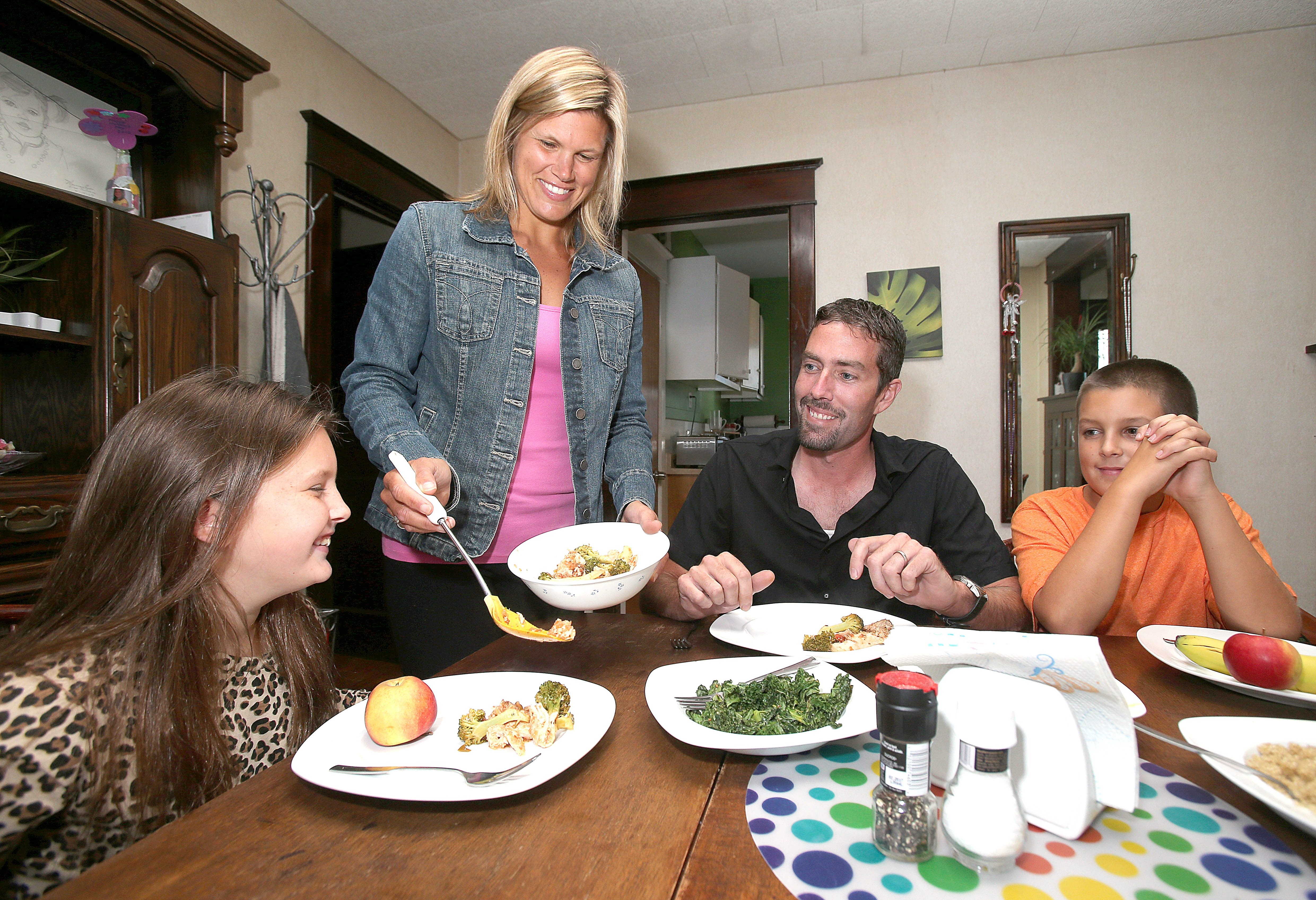 Rachel Miller serves dinner to her family, daughter Emma, 8, husband John, and son Cody, 12. Miller believes it is more cost-effective to go to the grocery store for whole foods instead of eating out.