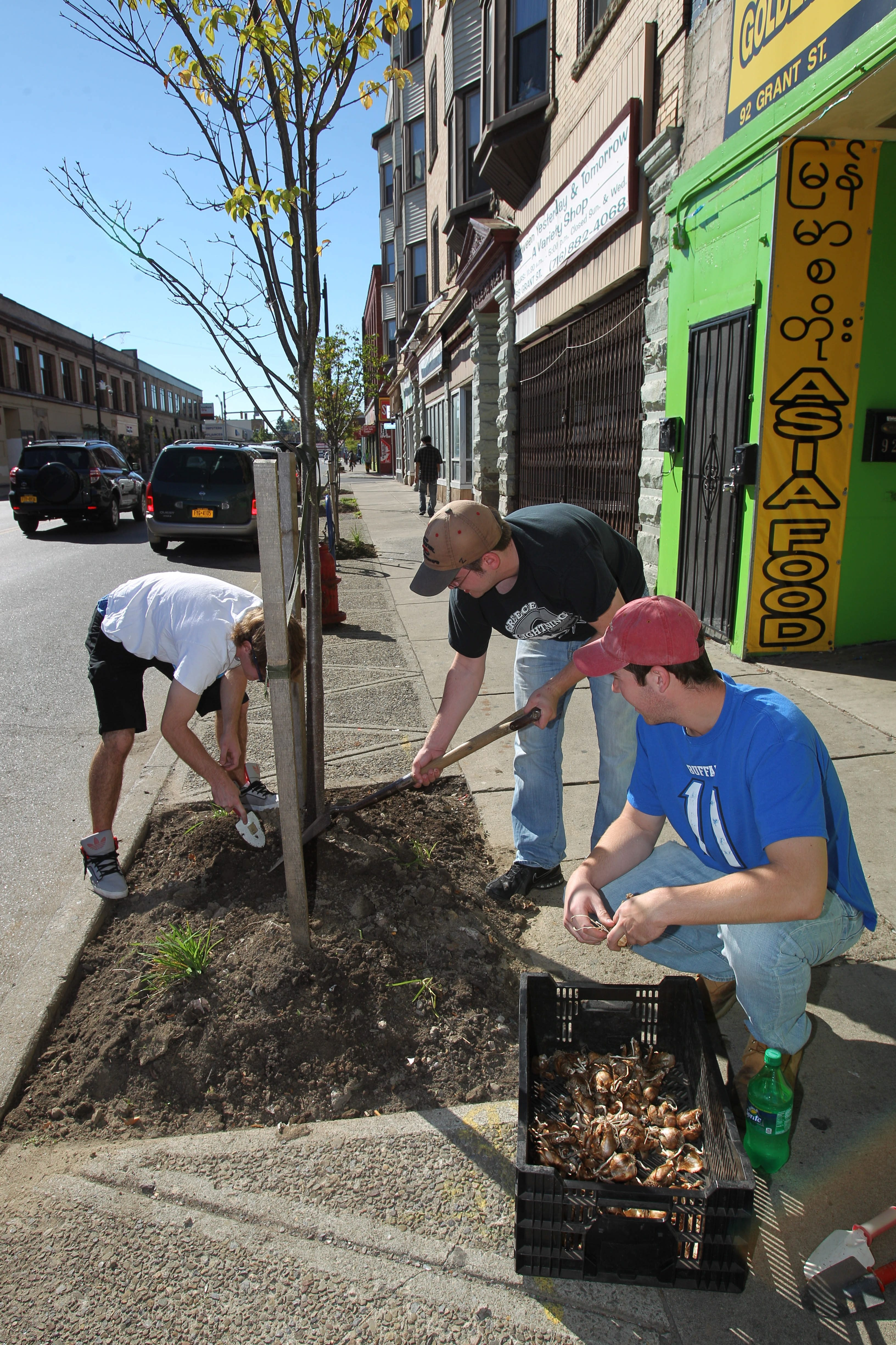 From left, Jeremy Bartula, Ryan Grace and Patrick O'Byrne, University at Buffalo Golfers Association members, work Saturday on Grant Street.