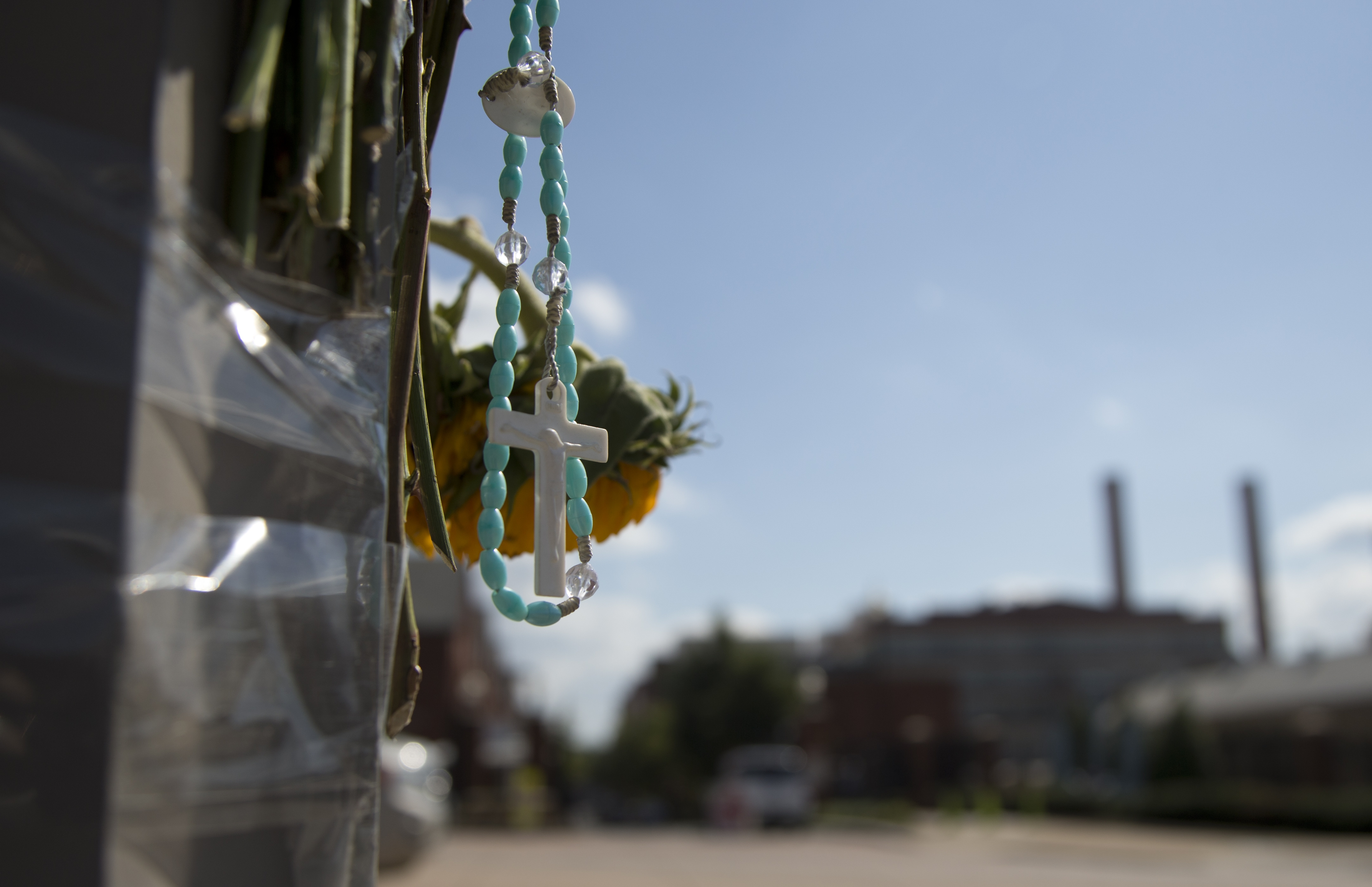 A rosary hangs Friday from a makeshift memorial across the street from the Washington Navy Yard, where 13 people were killed, including the gunman.