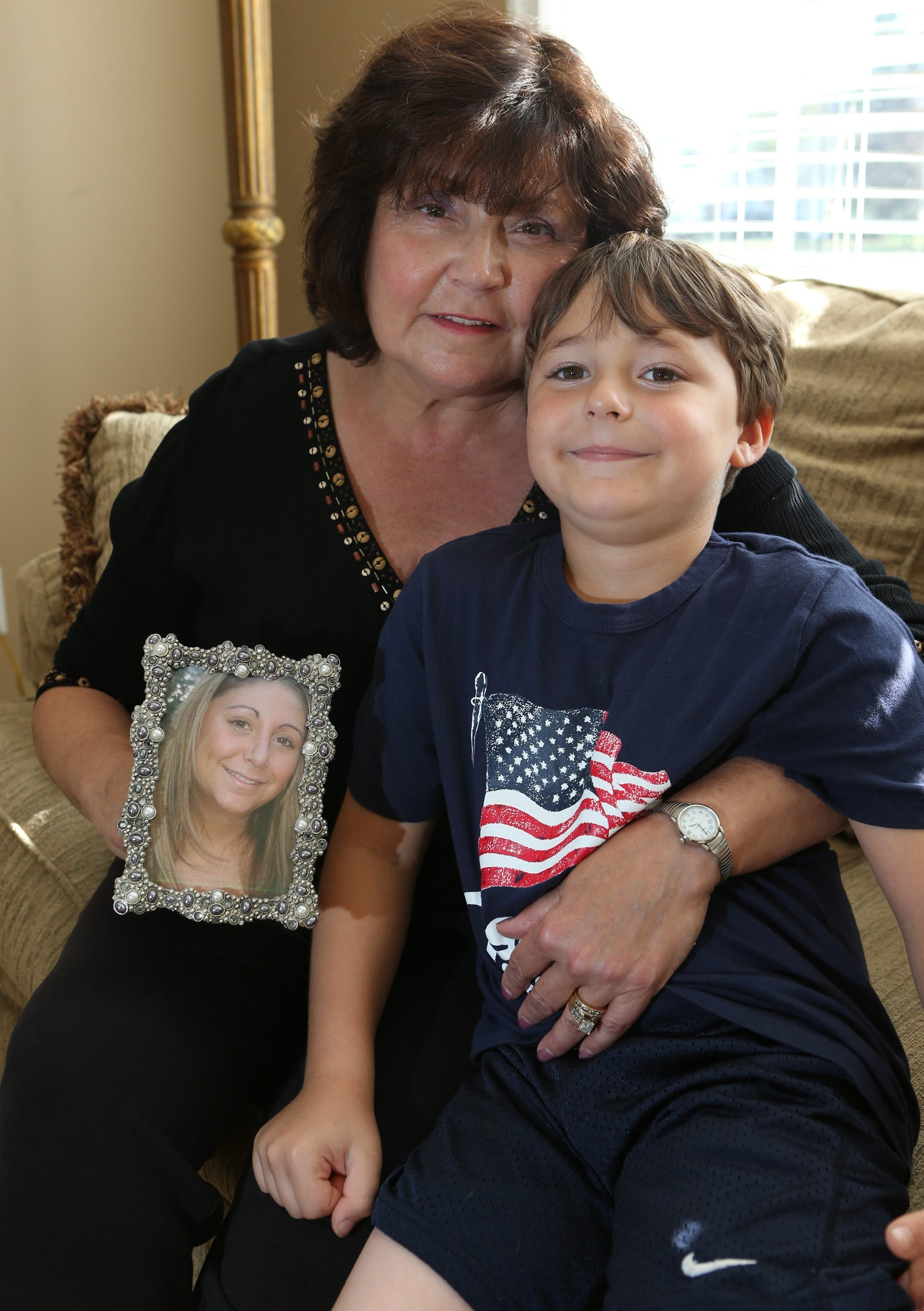 Sandy Mannella-Schwendler, with grandson Brandon Kane, 6, holds photo of daughter Elisa Mannella, who died in a car crash attributed to the effects of DXM on fiancé who was driving.