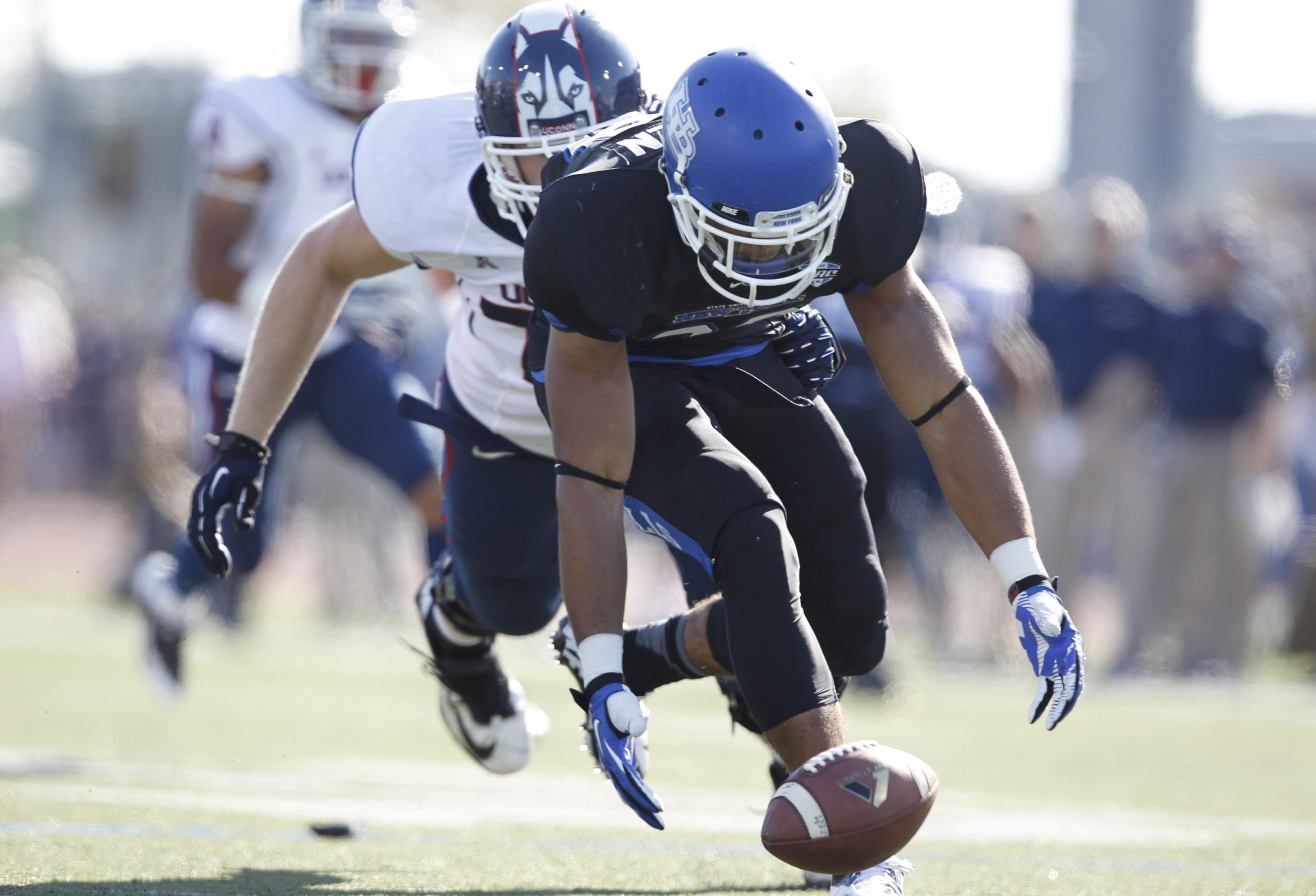 UB's Adam Redden scoops up a fumble in the first quarter against Connecticut.