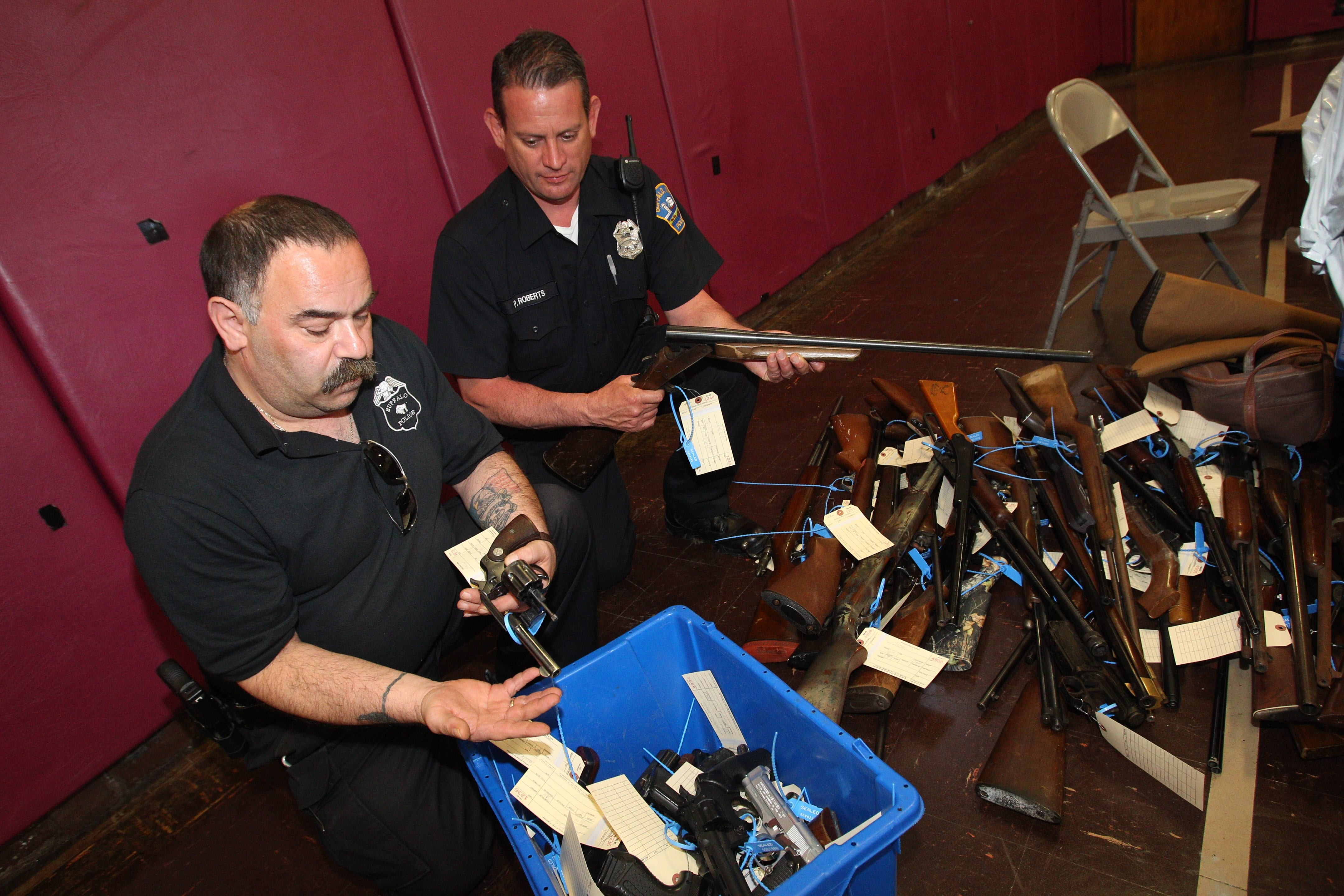 Buffalo Police Officers Armando Cordone, left, and Paul Roberts hold guns that were turned in in May when the city of Buffalo held a gun buyback at four different locations. The state announced a gun buyback program today.