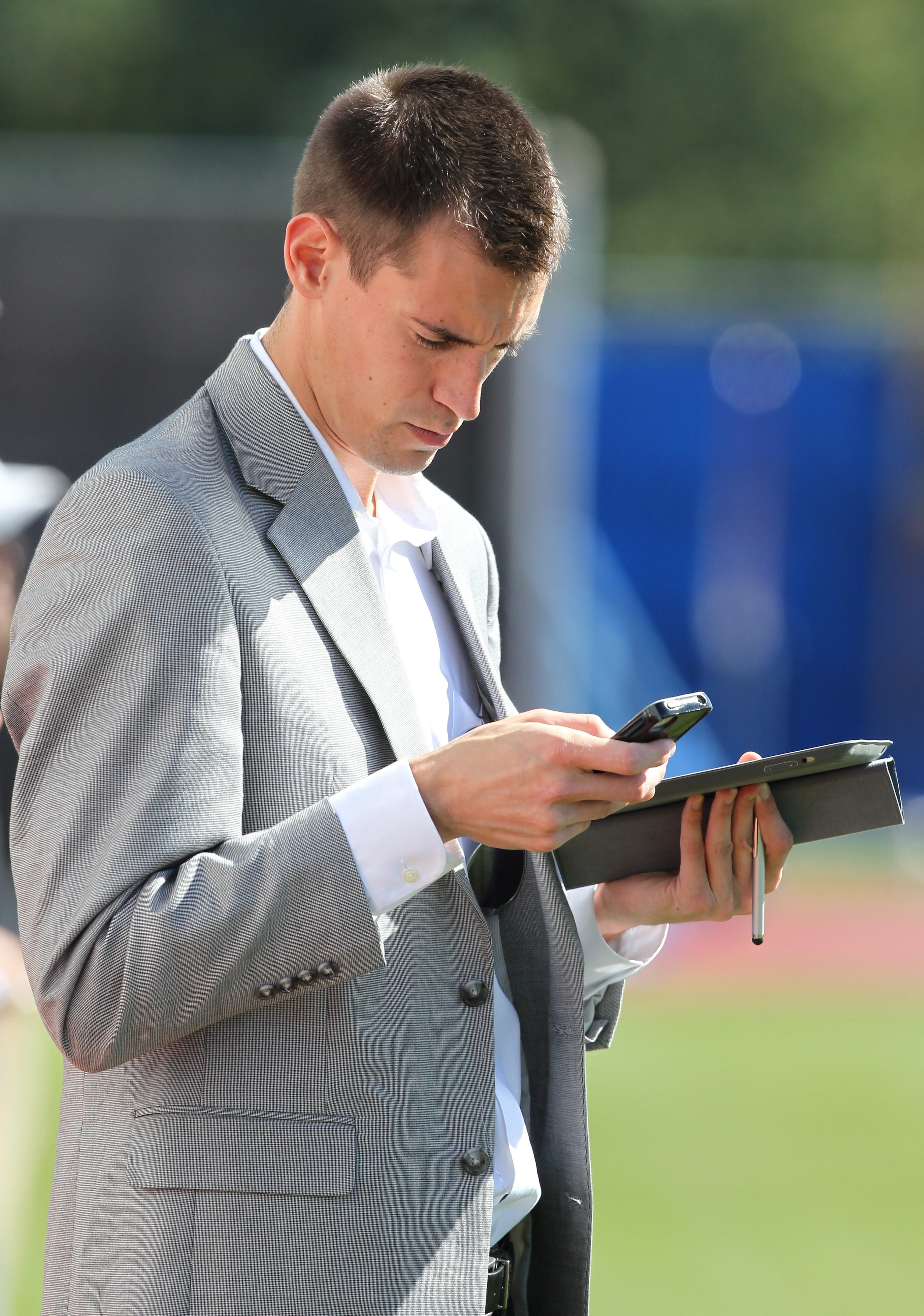 WGR's Joe Buscaglia checks his phone and notes while covering the Bills from the sideline during practice Wednesday at the team's practice field in Orchard Park.