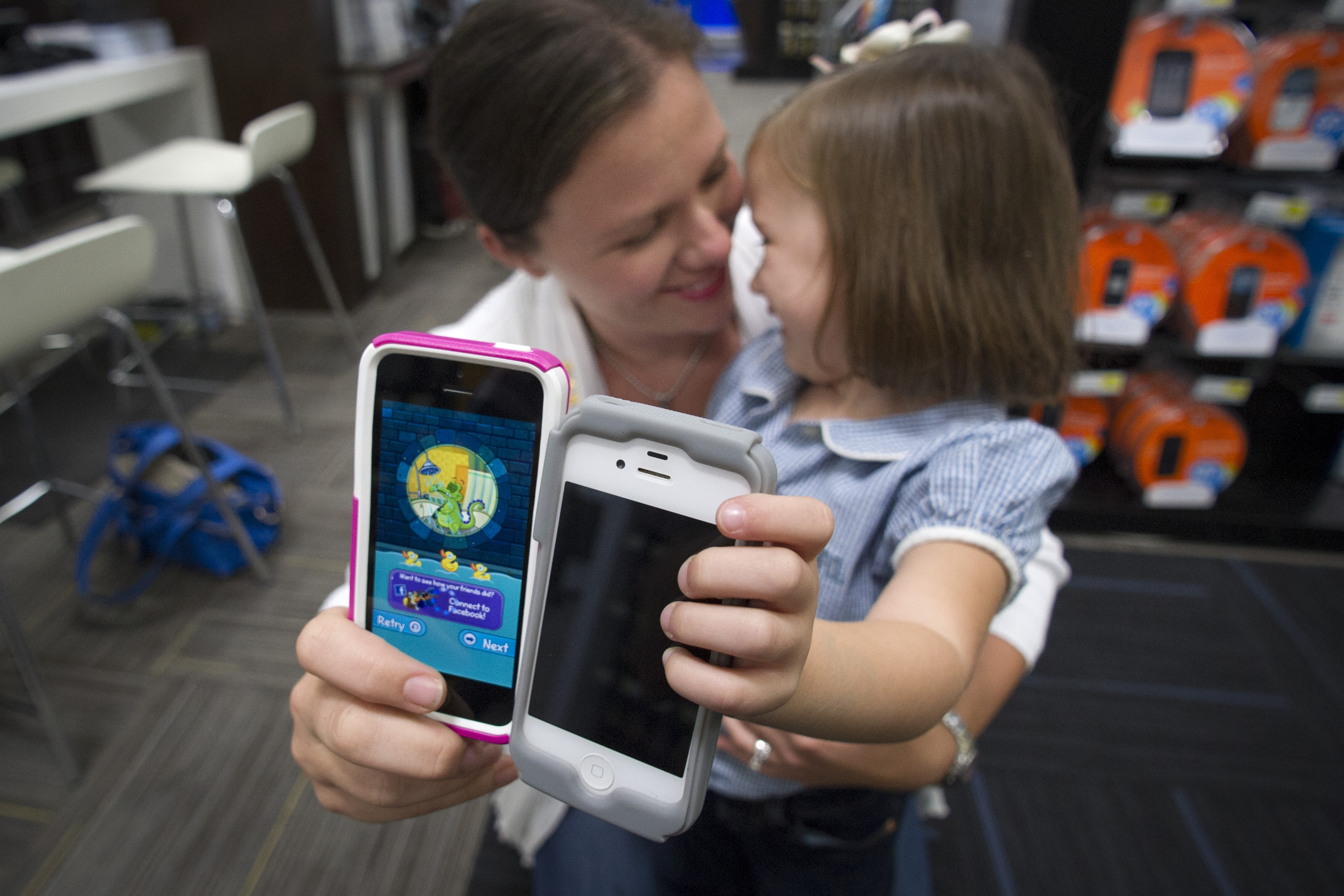 Isabel Ramo, 3, holds an iPhone 4 while her mom, Christen Ramo, shows offer her new iPhone 5s.