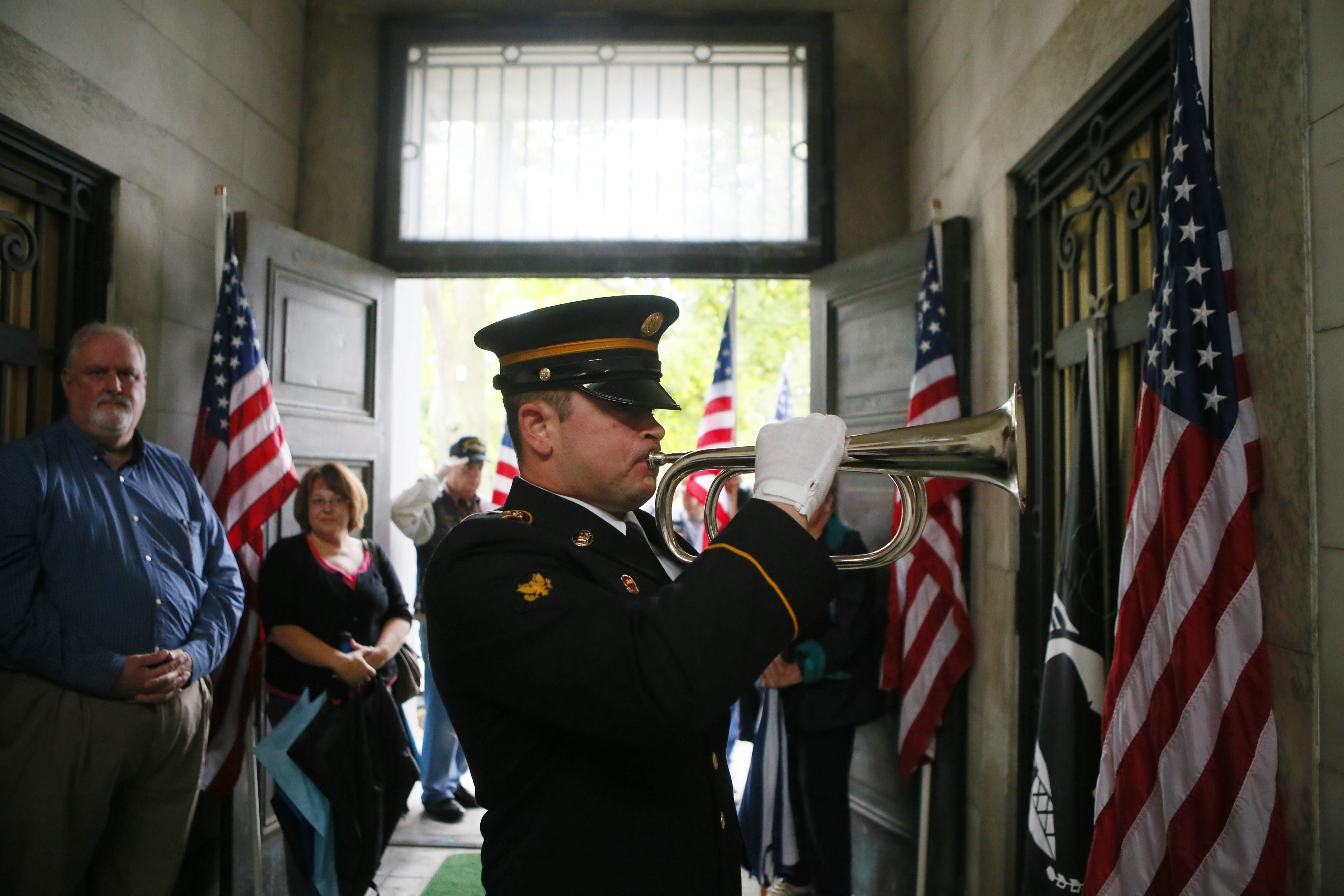 Spc. Phil Rosati of the honor guard plays taps during a remembrance event for Capt. William C. Glasgow, a highly decorated fighter pilot and POW in World War II who was killed at age 27 in crash of his experimental plane at Ohio air show in 1945.