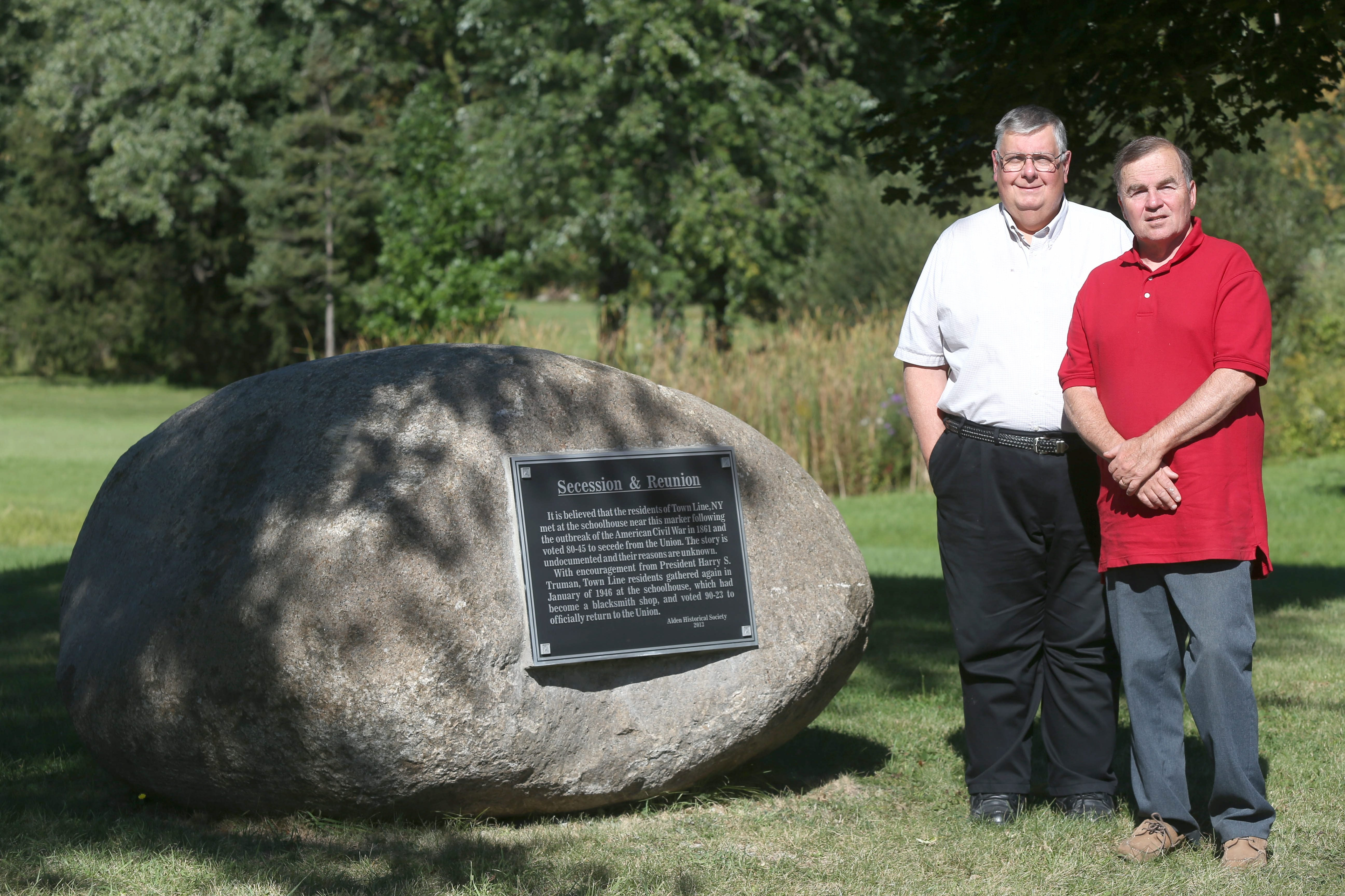 Gil Dussault, Alden Historical Society president, left, and society trustee Conrad Borucki stand near the new marker, which the society installed on Broadway near Town Line Road.