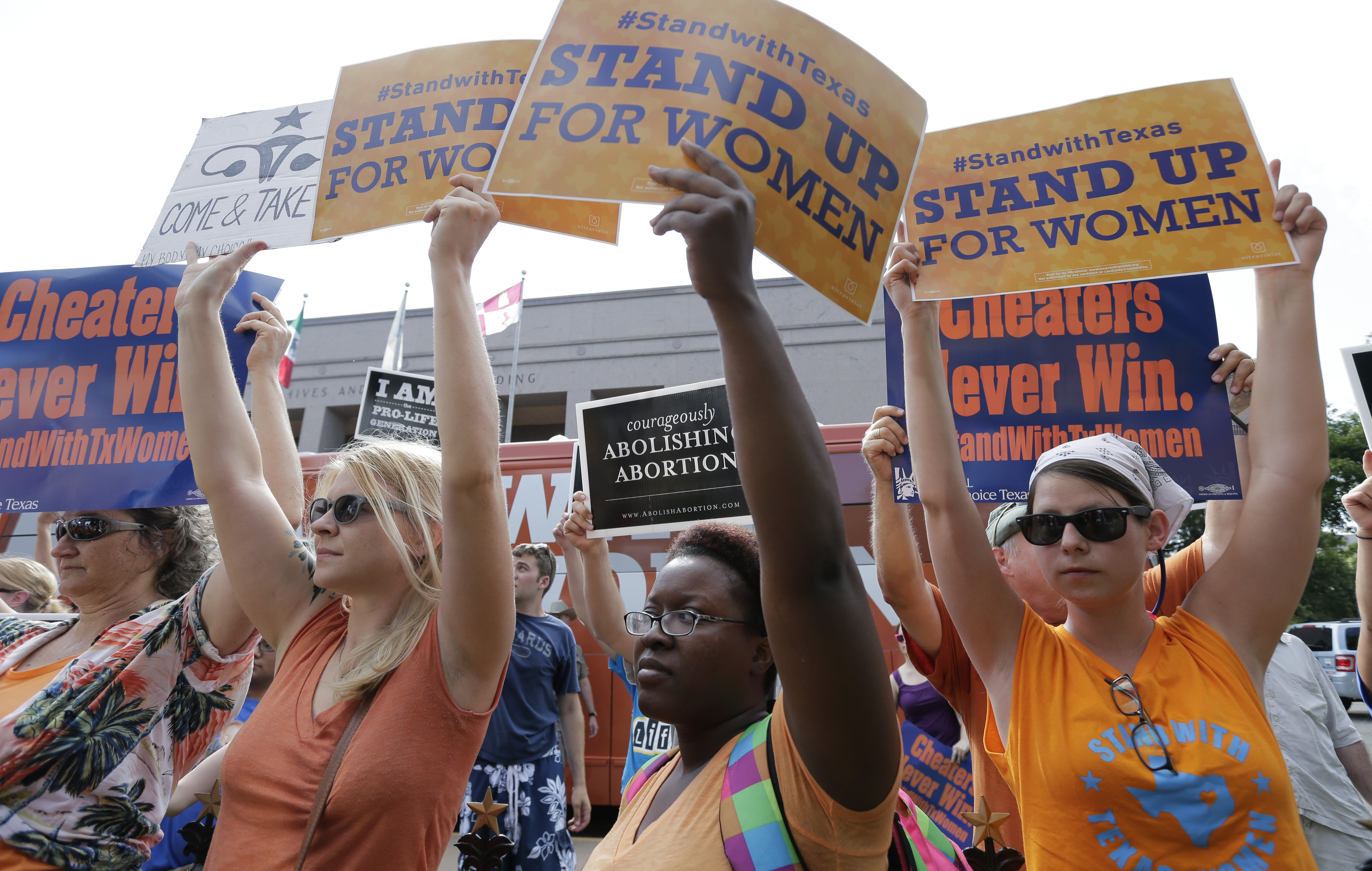 Opponents and supporters of an abortion bill hold signs outside the Texas Capitol, in Austin, Texas, in July.