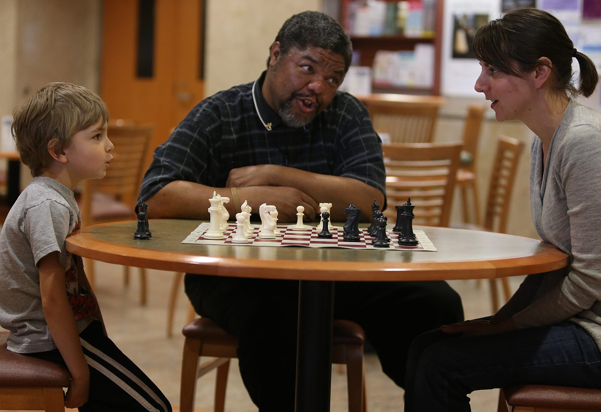 Michael A. McDuffie, of the Archangel 8 Chess Academy in Buffalo, center, gives advice to Jen Mattimore, right, of Buffalo, and her son Waylon at a chess open house earlier this year at the Central Library. The next open house is from noon to 4:30 p.m. Sunday.
