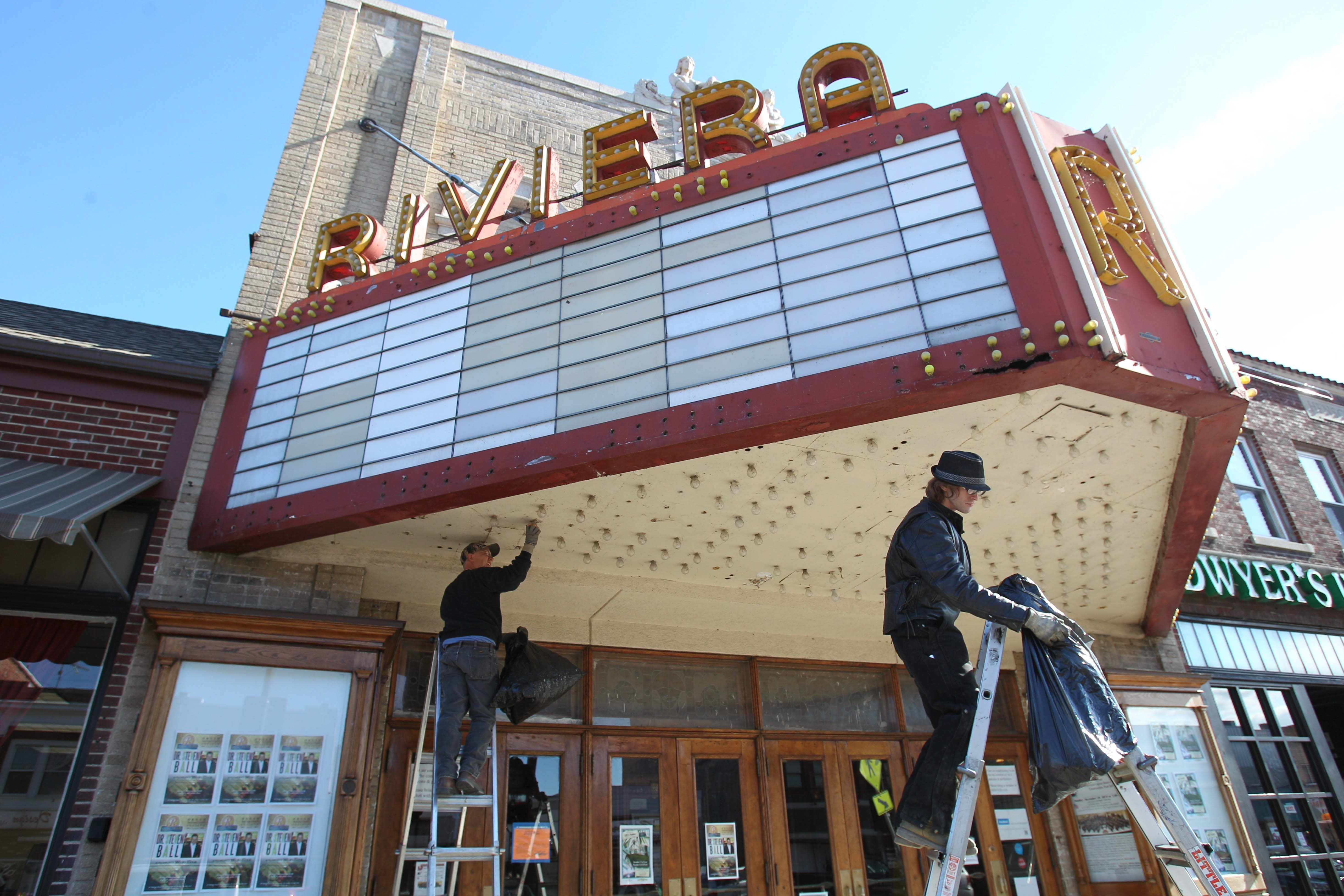 Larry Ester, left, and Joshua Nichols remove bulbs from the marquee at the Riviera Theatre in North Tonawanda on Monday. The sign is undergoing a $275,000 restoration.
