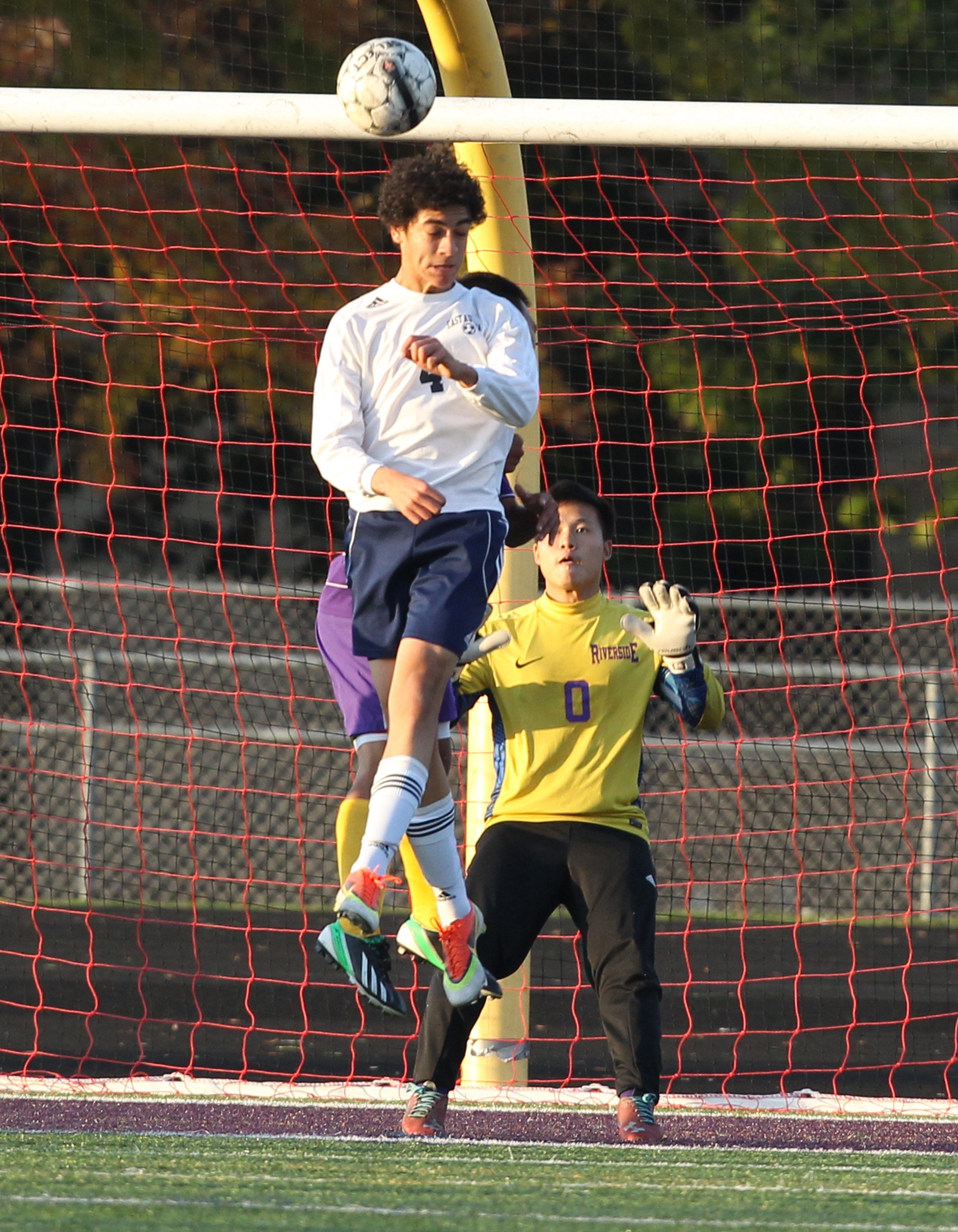 East Aurora's Ben Ingram heads the ball and scores a goal over Riverside goalie Sah Moo in the Class A-2 championship.