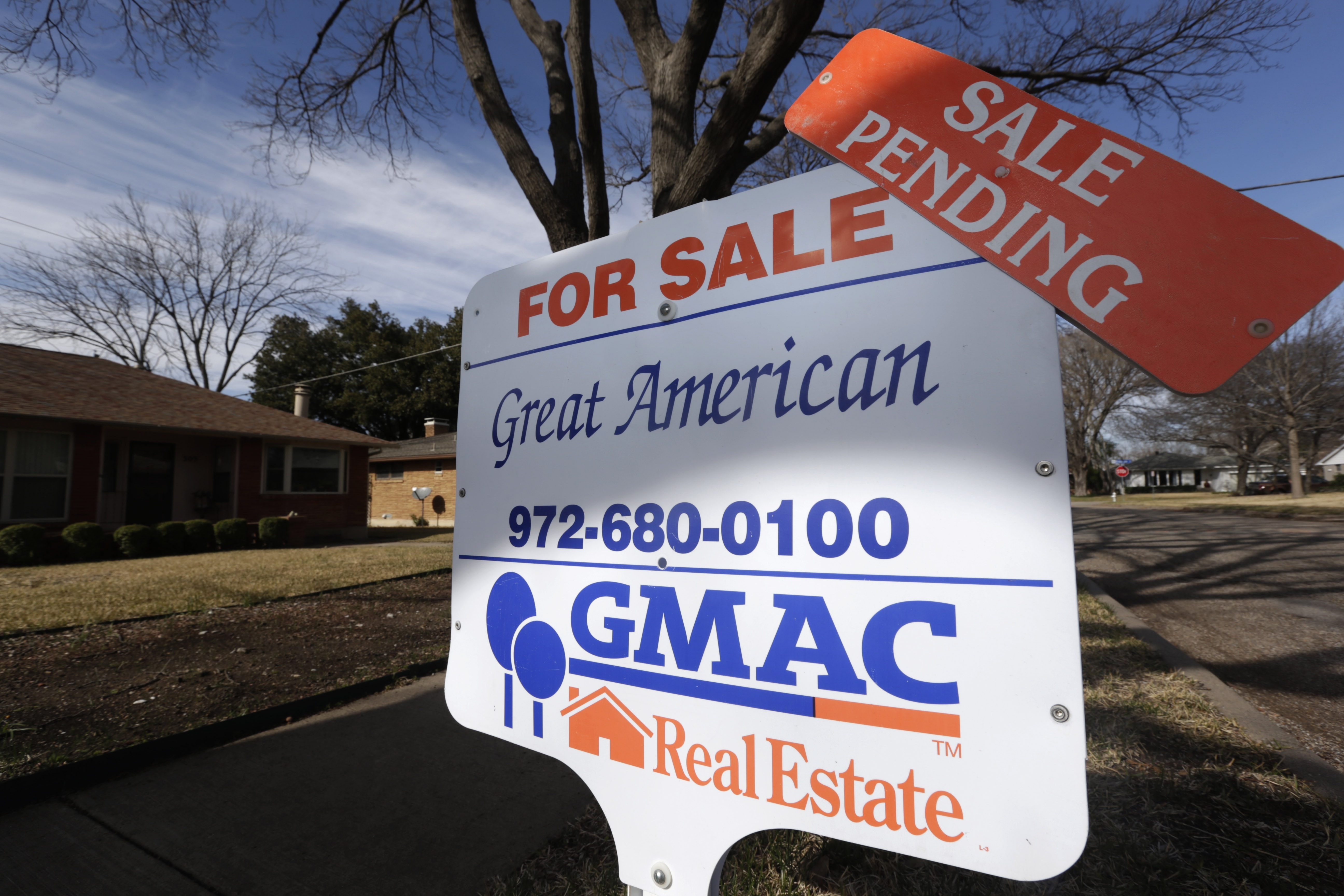 A sale-pending announcement sits atop a for-sale sign in a home's yard in Richardson, Texas.  The number of Americans who signed contracts to buy homes dropped sharply in September 2013 to the lowest level in nine months.