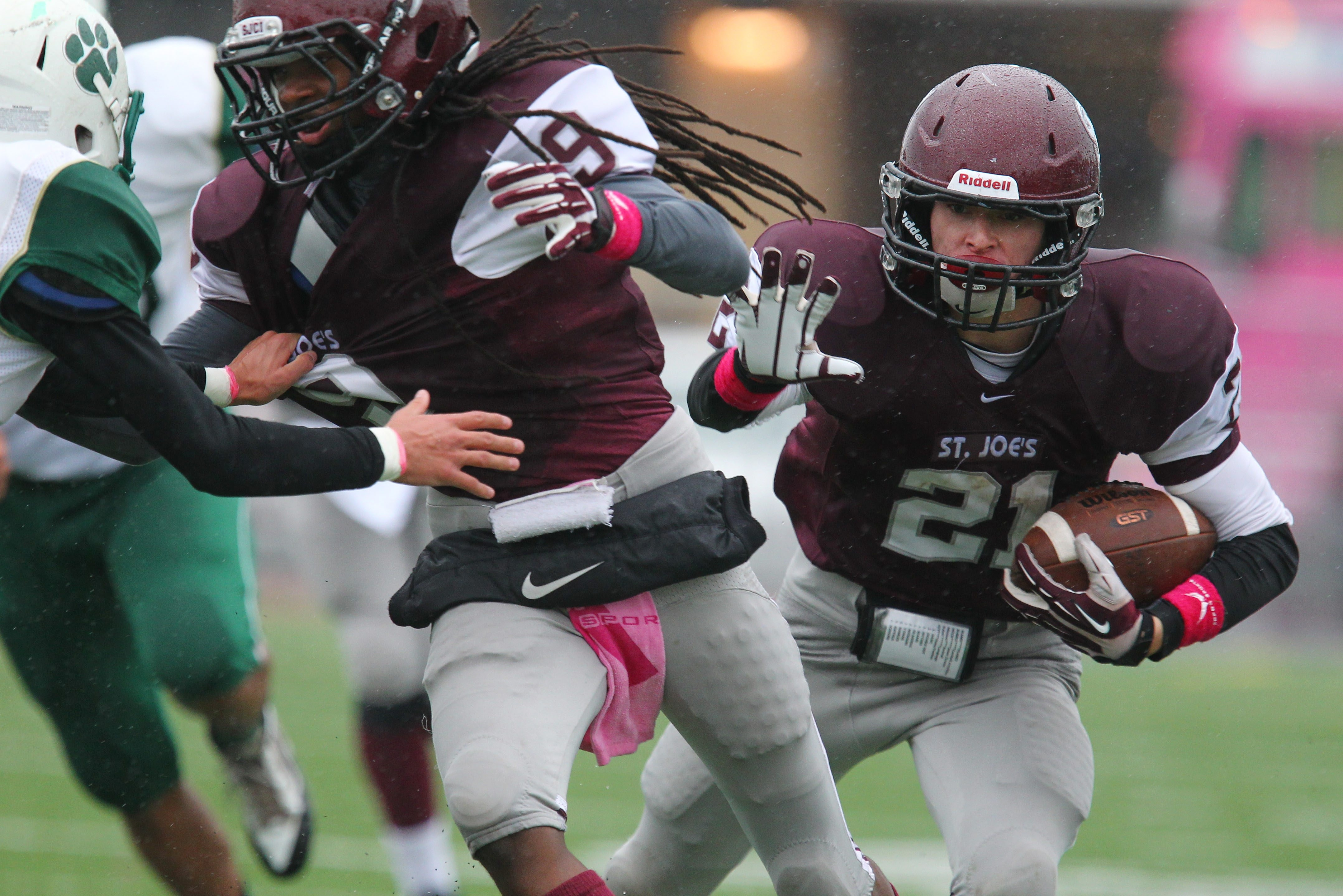 Ryan Conschafter (21) gets a block from St. Joe's teammate Alimayu Akono during the Marauders' 15-6 victory over visiting Bishop Timon-St. Jude. St. Joe's plays at rival Canisius next week.