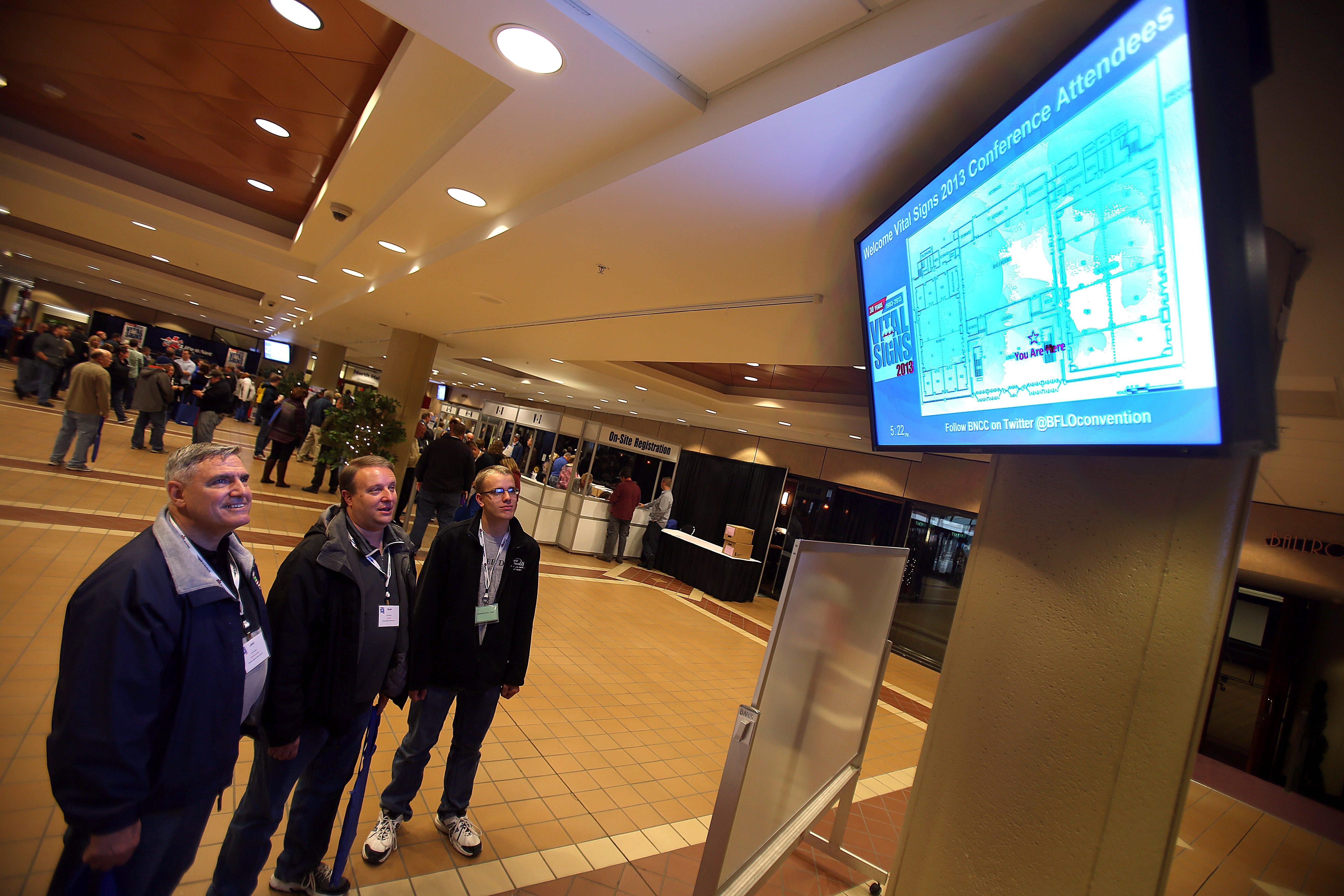 Exploring the new wireless network at the Buffalo Niagara Convention Center Friday are Long Island emergency medical technicians, from left,  John Hassett, Scott Glazer and Matt Glazer.