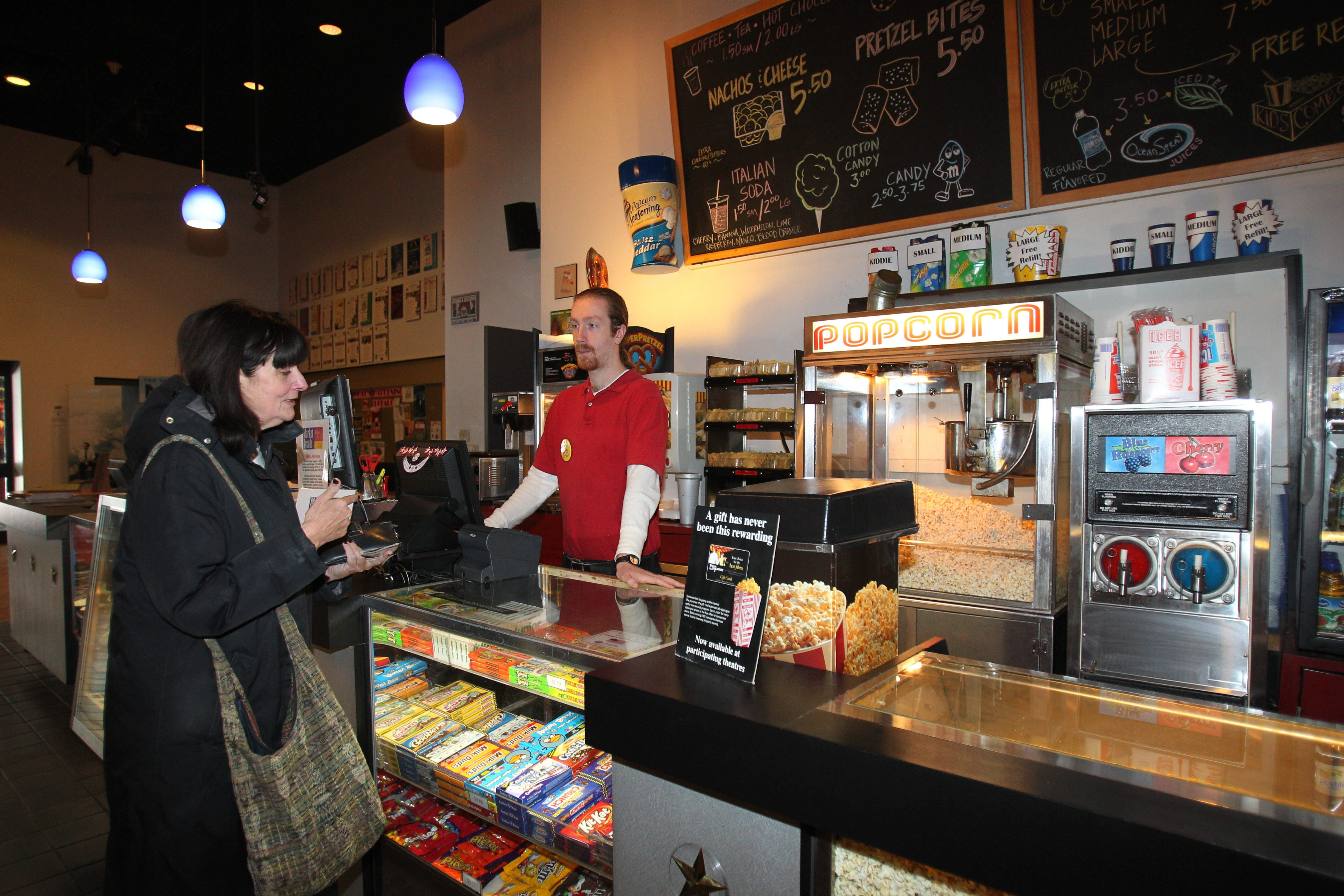 """Jeffrey Melvin serves Catherine Mettille at Market Arcade concession stand as theater future reaches """"crunch time."""""""