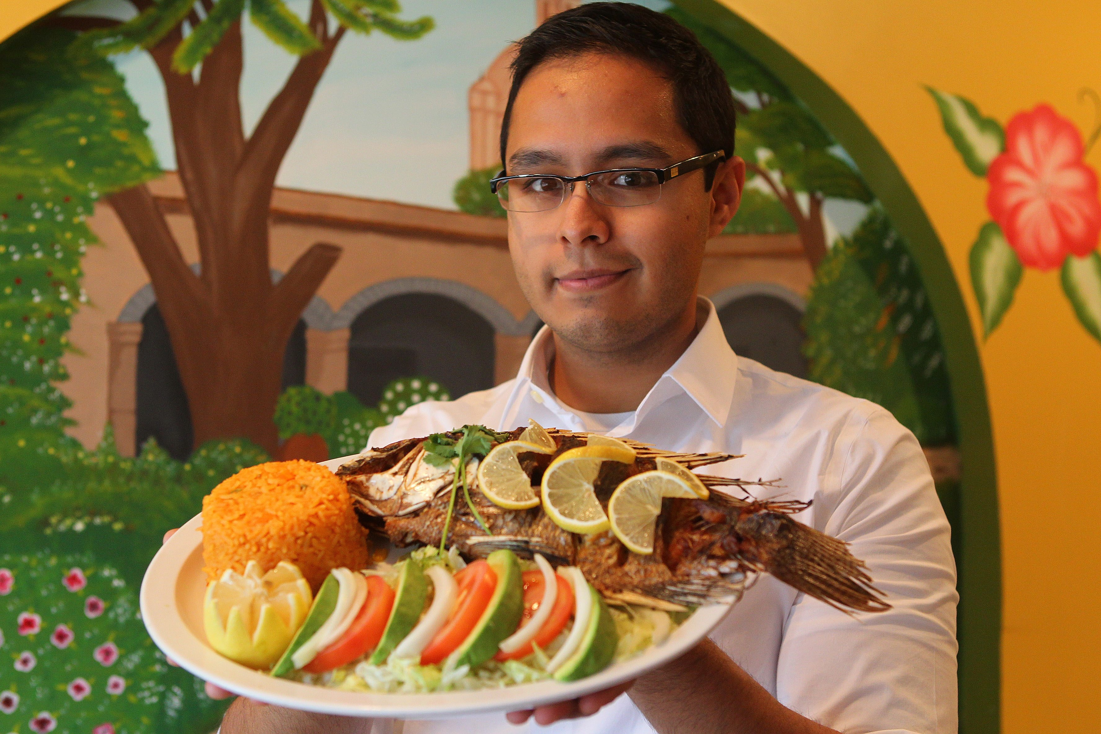Server Alexander Audelo displays a whole fried fish at El Ranchito in Clarence.