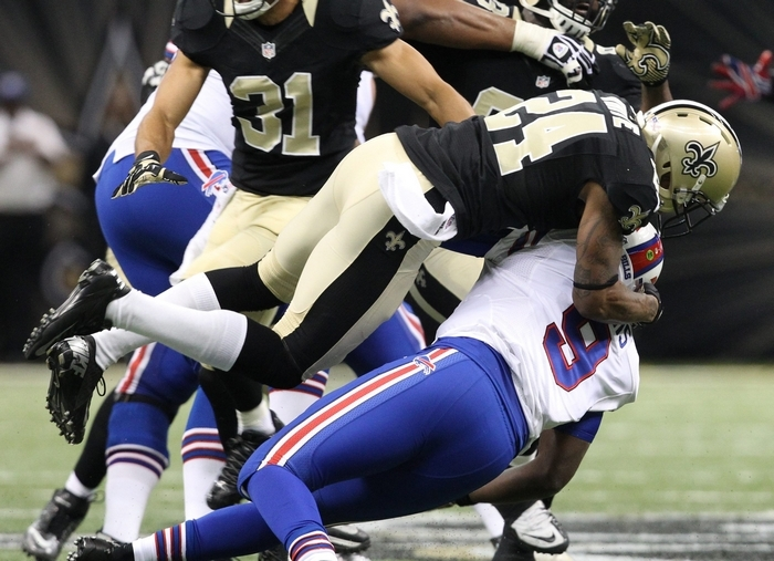 Bills quarterback Thad Lewis is hammered and forced to throw an incomplete pass by Saints cornerback Corey White in the third quarter Sunday. (James P. McCoy/Buffalo News)