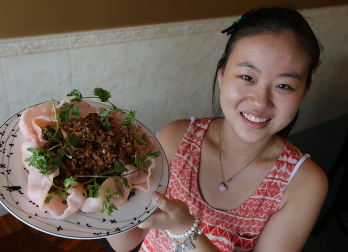 Hostess Teresa Lin proudly displays the crispy lamb, which is piled onto fish crackers and eaten like Chinese nachos.  (Charles Lewis/Buffalo News)