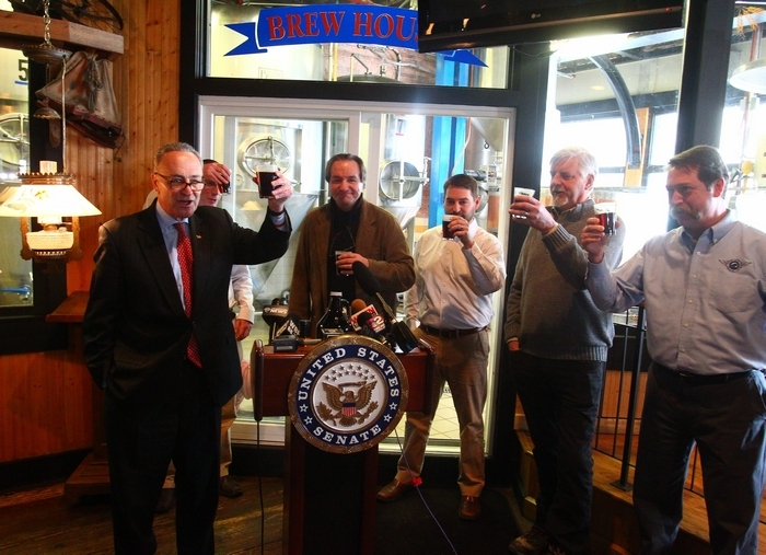 Sen. Charles Schumer offers a toast from lectern at news conference in Pearl Street Grill & Brewery as, from right, Tim Herzog, Doug Swift, Jeff Ware, Earl Ketry and Matt Kahn back his Small BREW Act. (John Hickey/Buffalo News)