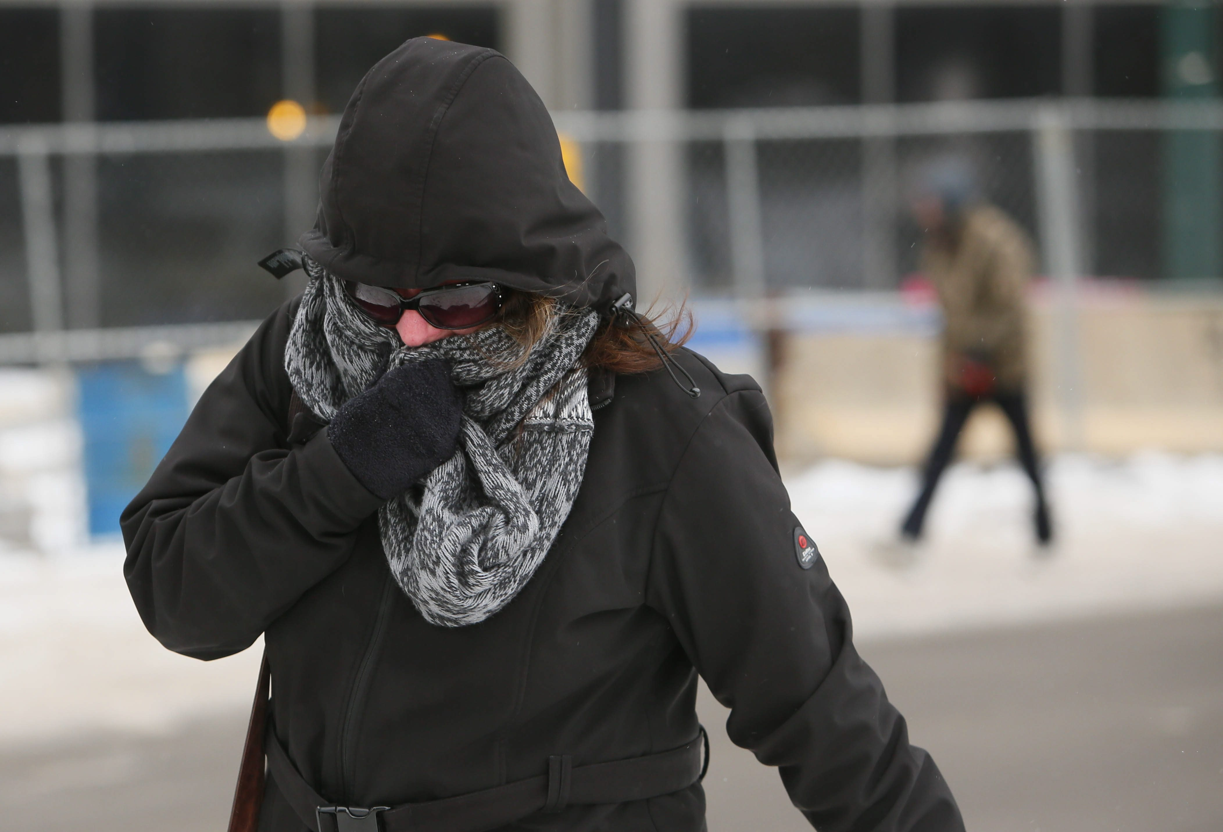 Jeanine Watson tries to shield herself from bitter cold and wind Wednesday in Lafayette Square.