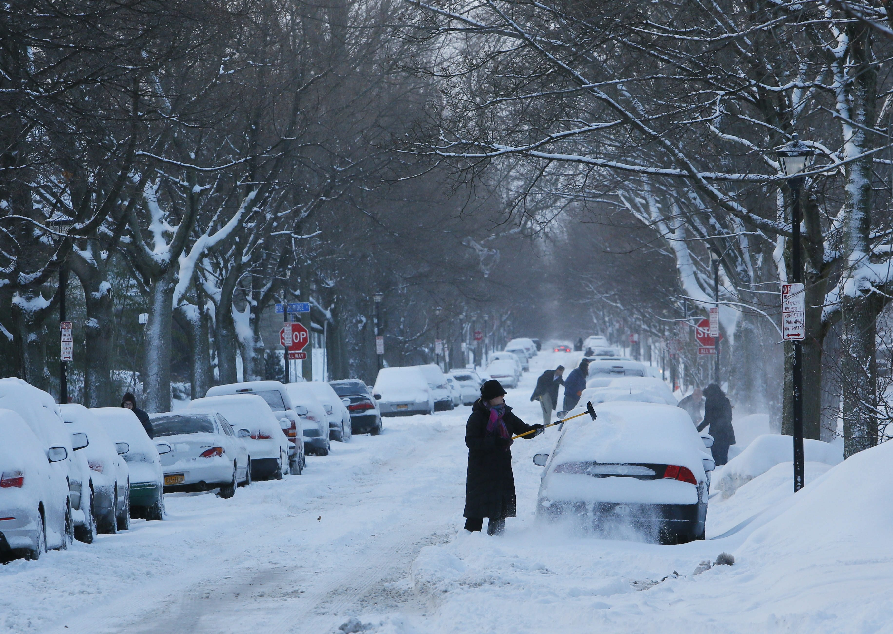 Residents of Norwood Avenue in Buffalo sweep off their cars early Monday morning after a night of snowfall.