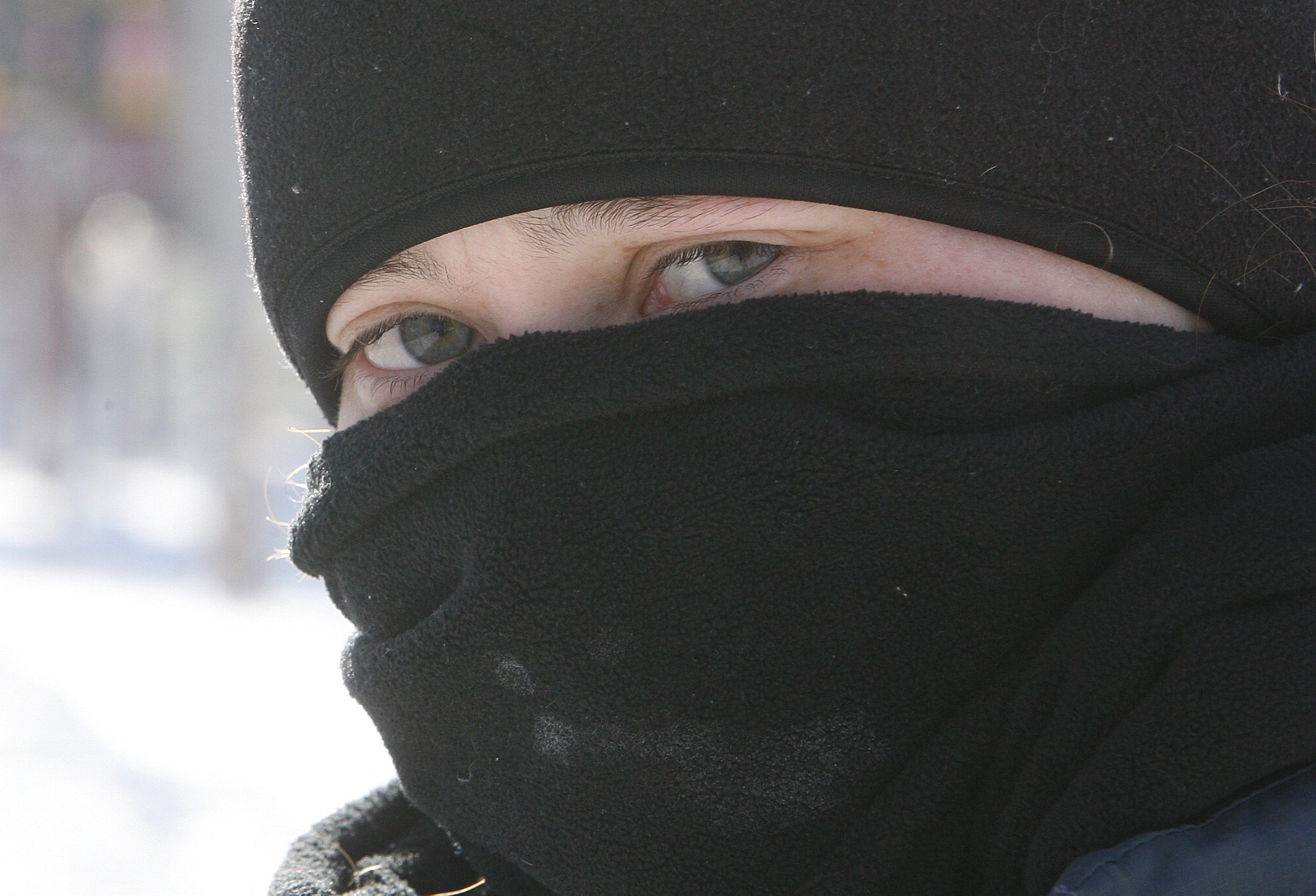 Robyn Baker exposes as little skin as possible Monday as she waits for a bus along Transit Road in Amherst on Monday.