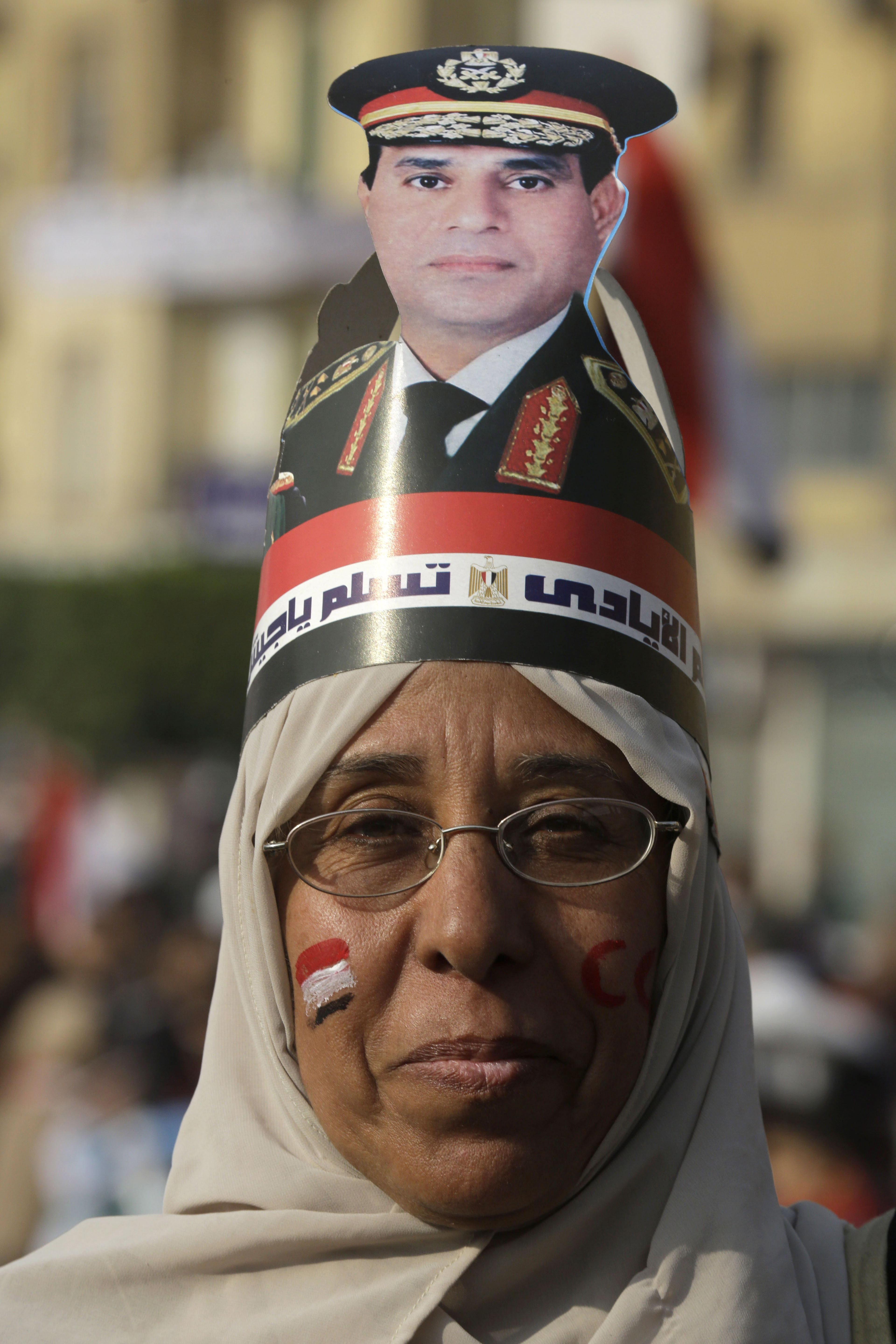 A man wears a picture of Egypt's defense minister at a rally commemorating the country's 2011 uprising.