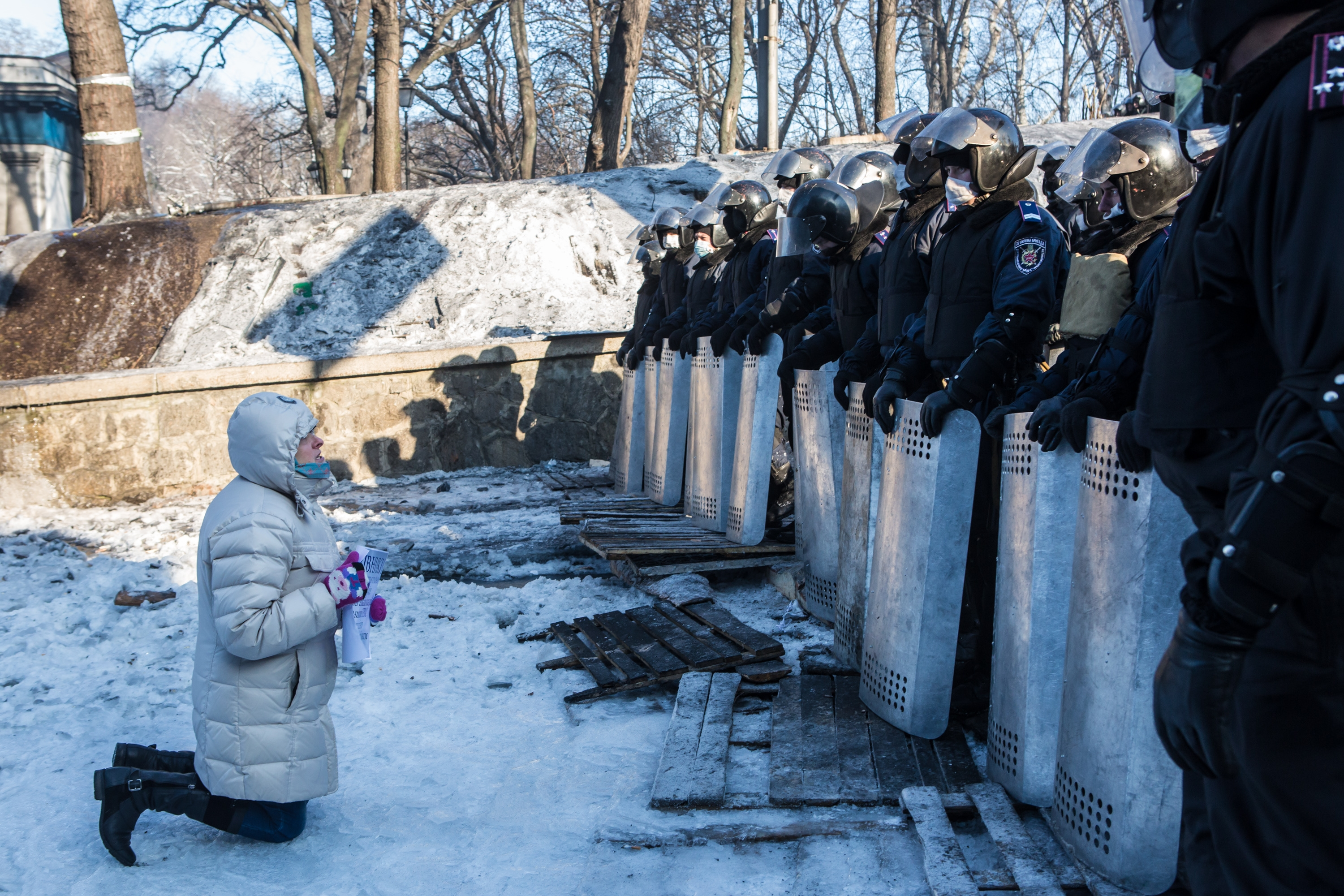 A woman prays in front of a line of police officers Friday on the street near the Cabinet of Ministers building and Dynamo stadium in Kiev, Ukraine.