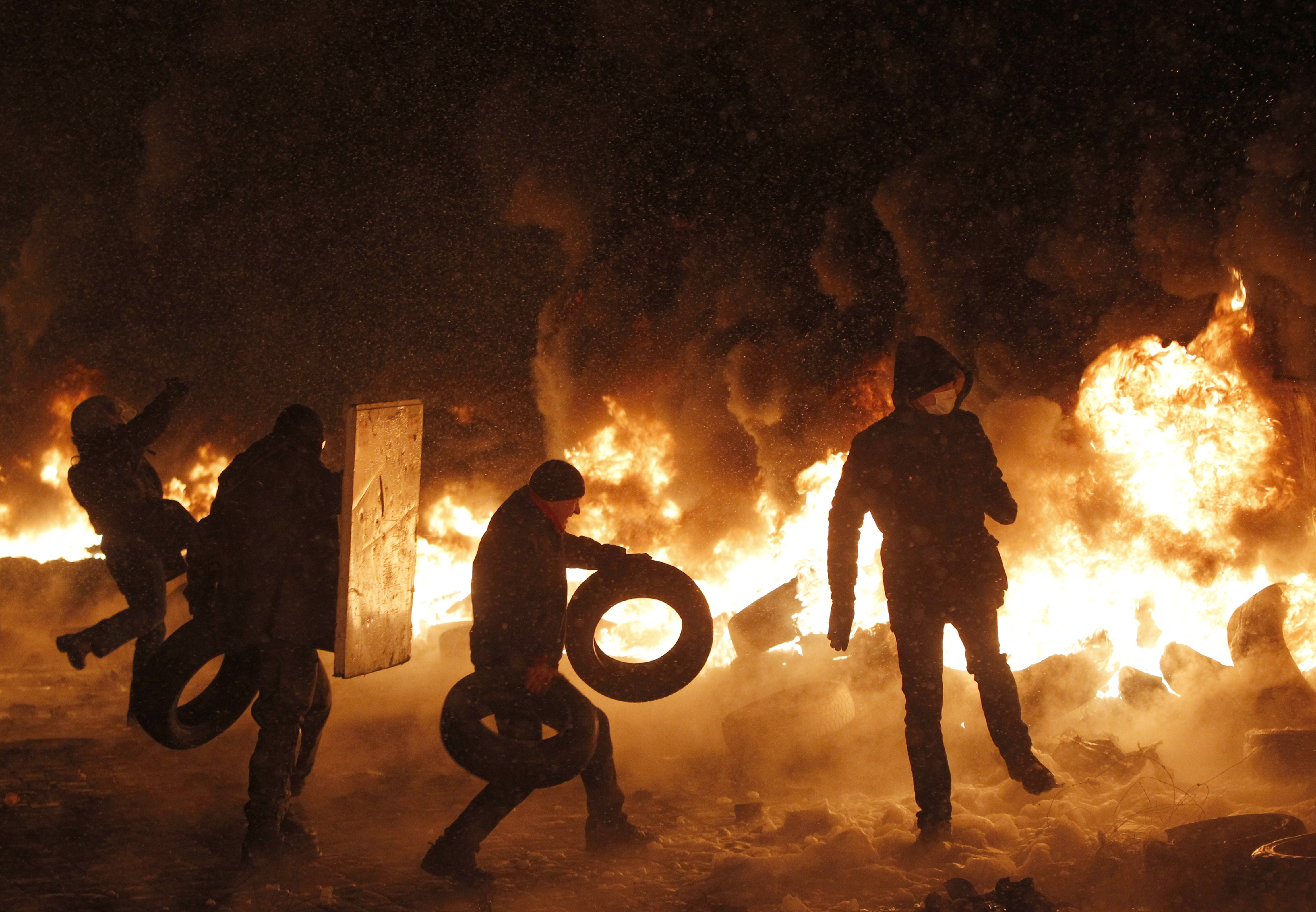 Protesters throw tires onto a fire during clashes with police Wednesday in central Kiev, Ukraine.  One report said that four people were killed.