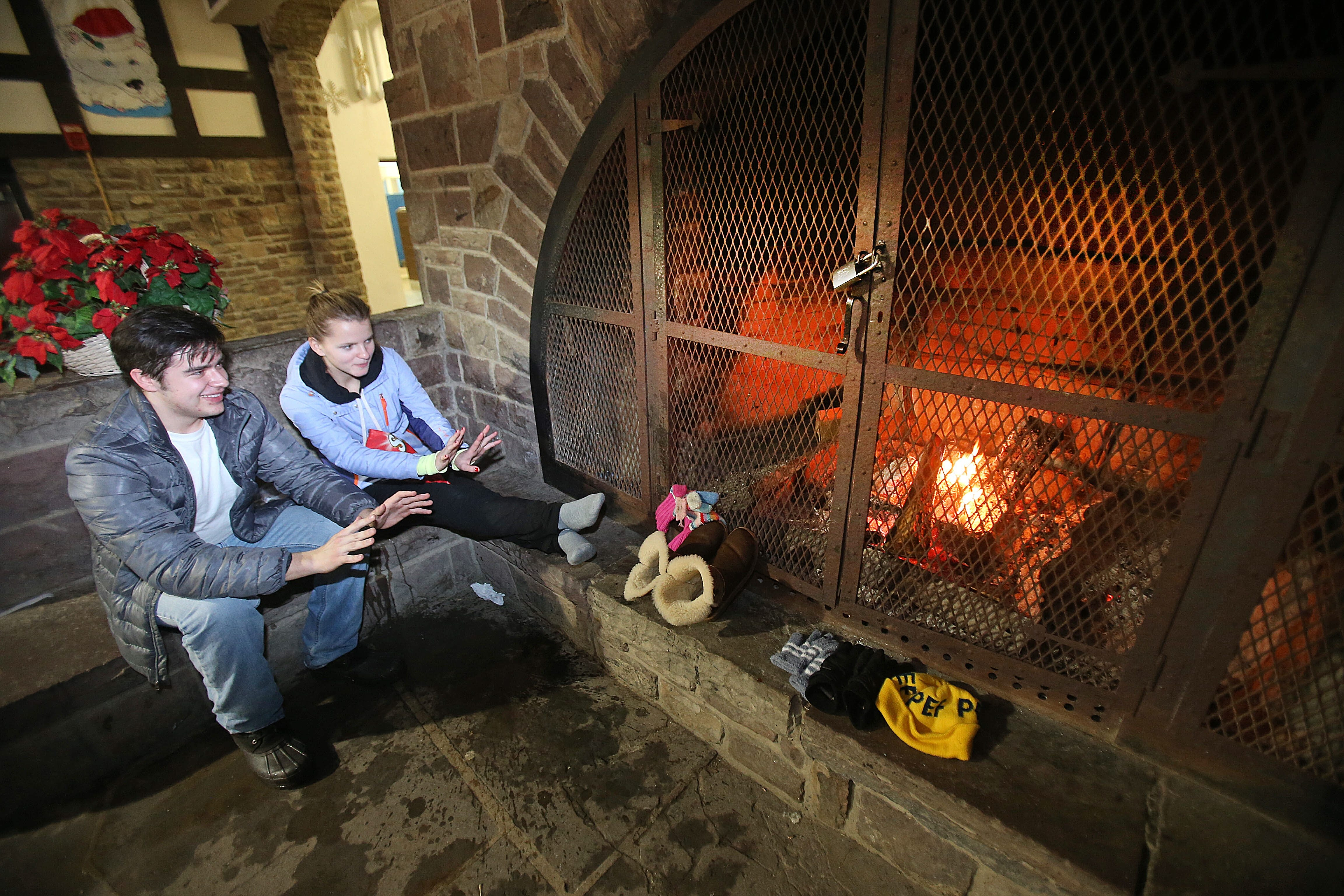 Vadim Fedoriskin, of Orchard Park, left, and Galina Zheliazniuk, of Amherst, stay warm. The fireplace at Chestnut Ridge Casino is a WNY favorite.  Sledders and family warm up after being outside on Friday, Dec. 27, 2013.  (Robert Kirkham/Buffalo News)