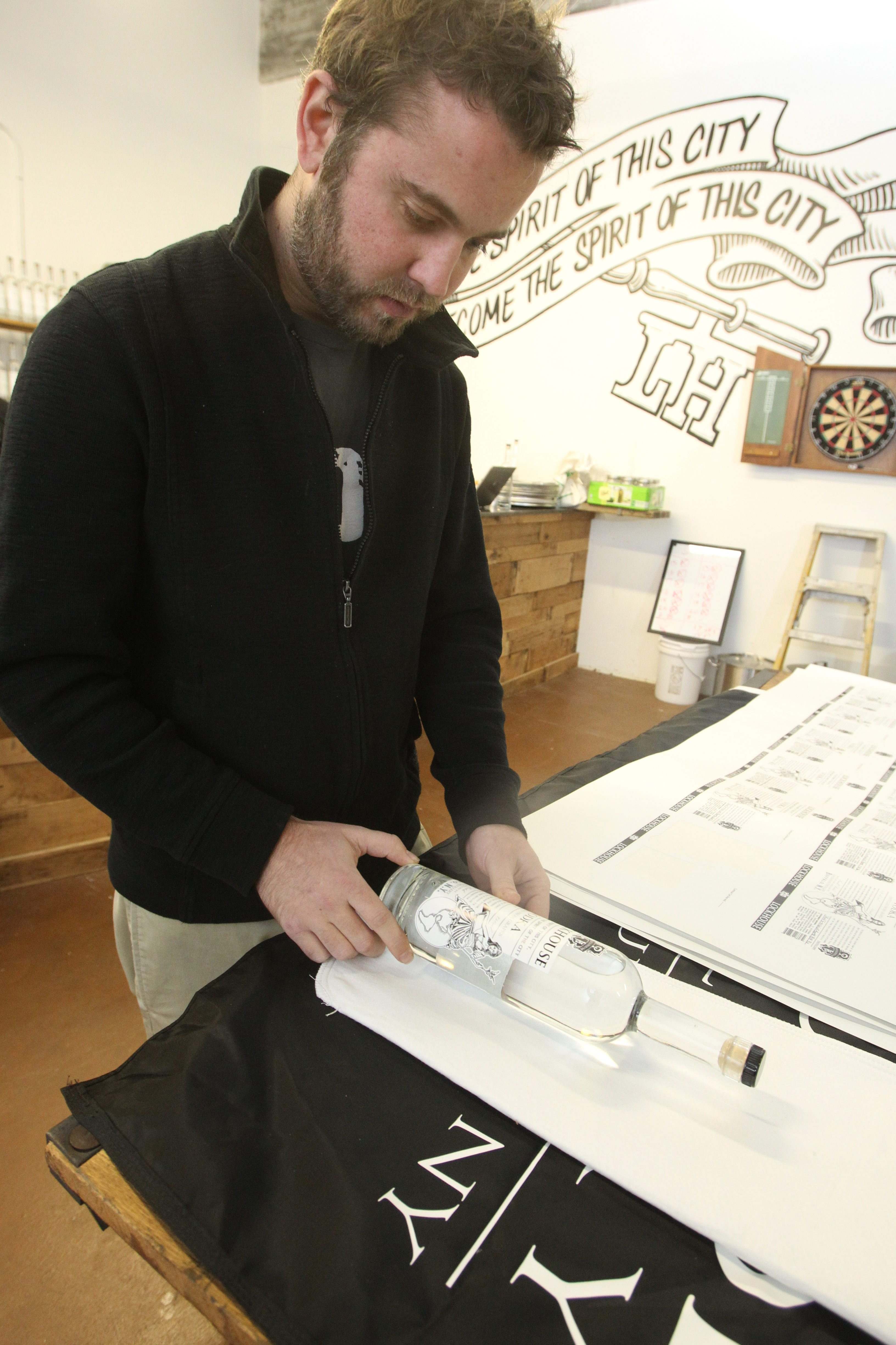Lockhouse Distillery Vice President Chad Vesseller puts labeling on bottles of vodka at the distillery in the Great Arrow Building in Buffalo in late November.