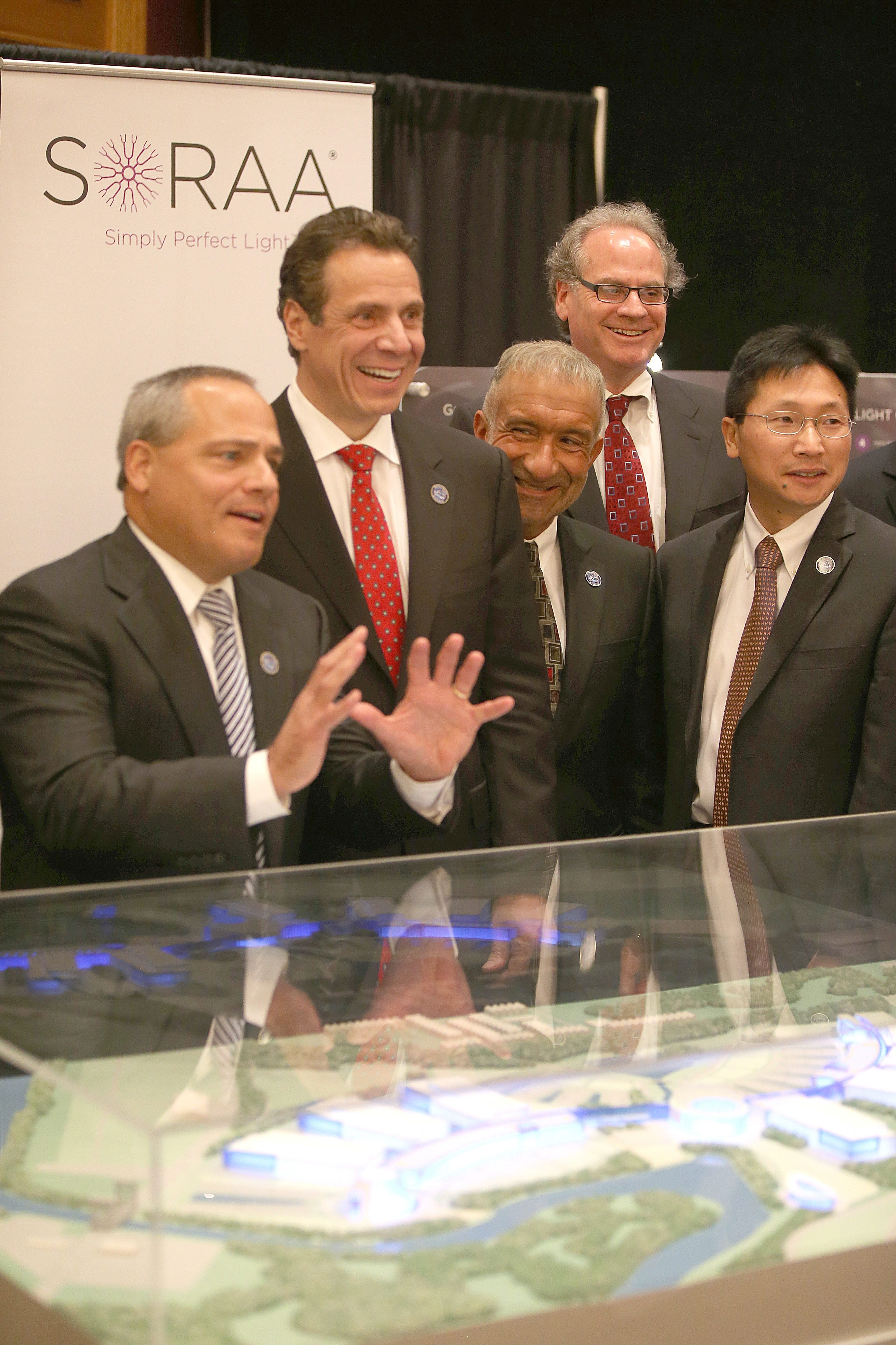 From left, Dr. Tom Caulfield, president and COO of Soraa, Gov. Andrew M. Cuomo, Alain Kaloyeros, Howard Zemsky and Dr. Zheng Xu, CEO of Silevo, announce the $225 million RiverBend project, shown in the rendering at the top of the page.   Robert Kirkham/Buffalo News