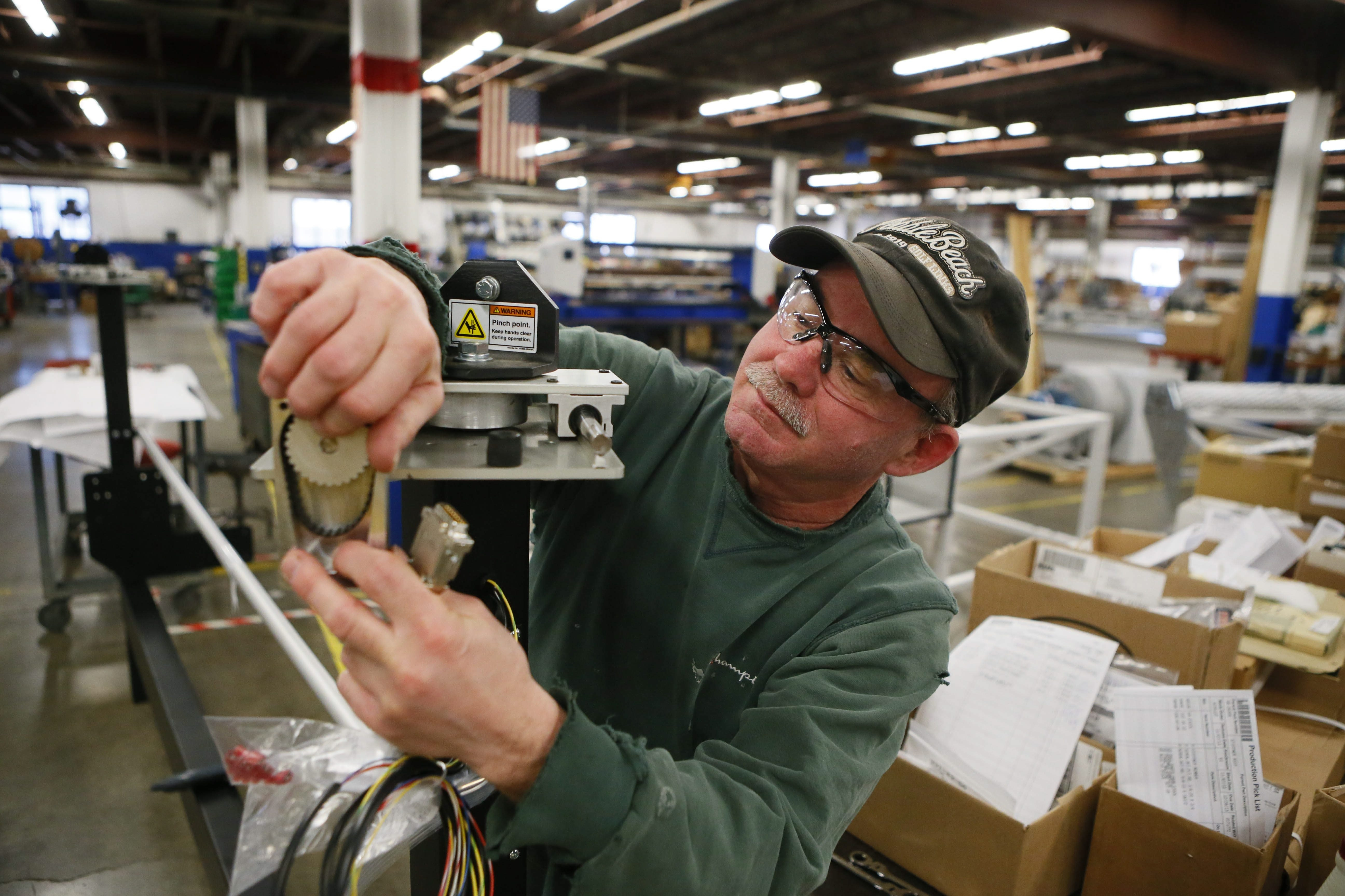 "Workers like Rob Kuhl, shown putting together an ""edge guide controller"" at Eastman Machine Co. in December, perform work that can't be easily sent overseas."