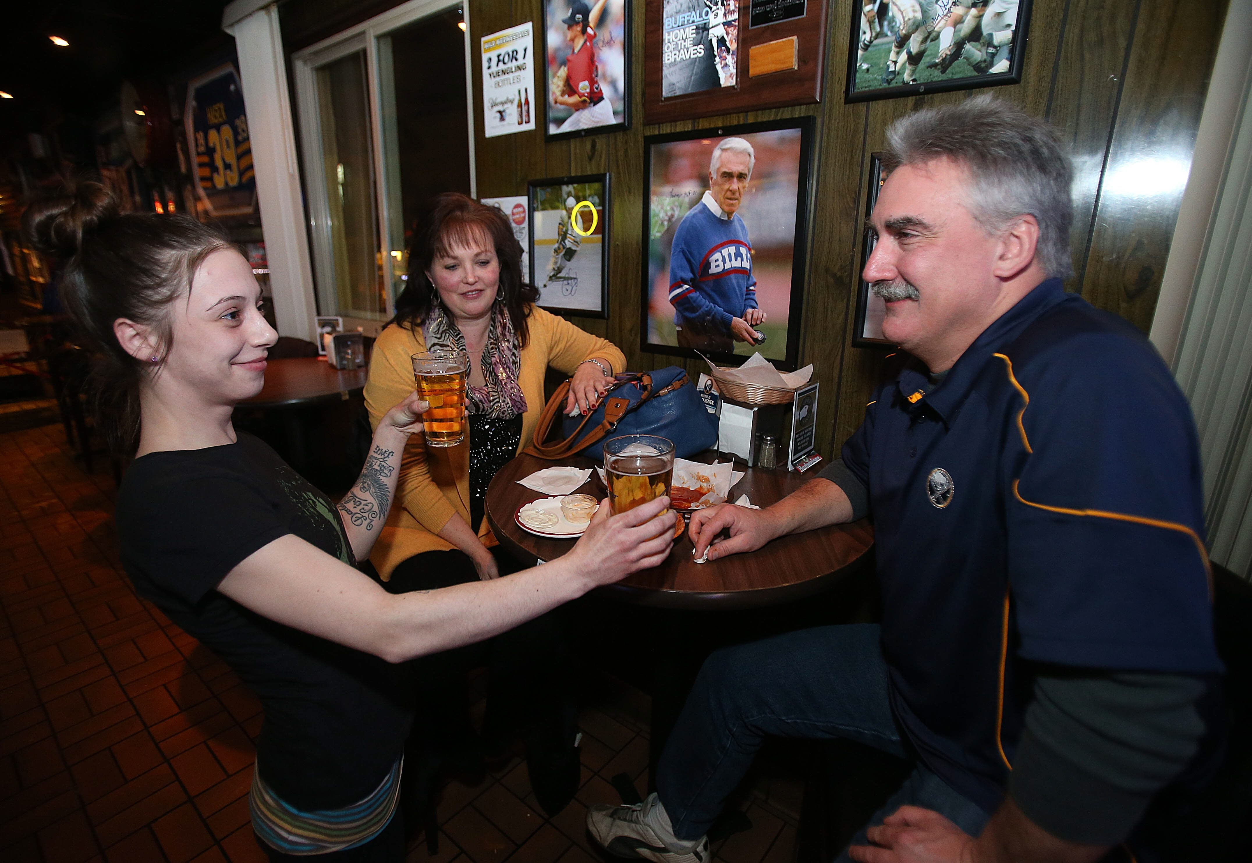 Ashley Gostomski delivers fresh pints of beer to Kim and Mike Green of Grand Island as they watch a Sabres game at Mitchell's Tavern in the Town of Tonawanda.
