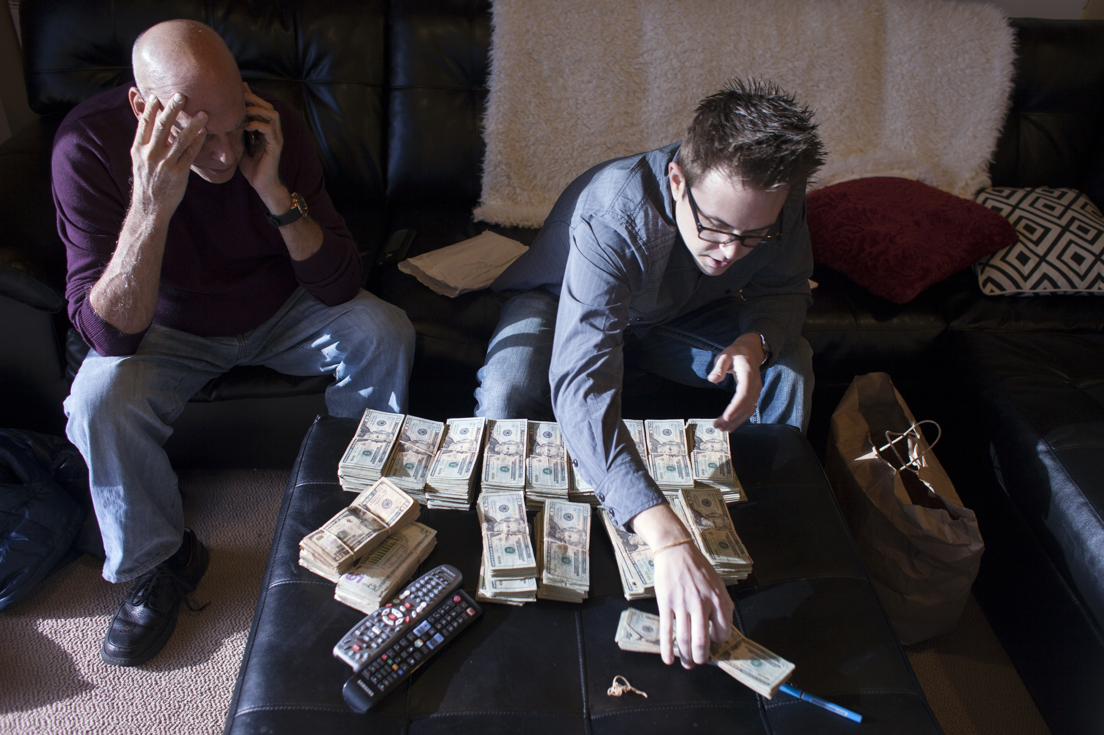 Ryan Kunkel, right, a co-owner of five marijuana dispensaries, counts tens of thousands of dollars cash beside his business partner, Joel Berman, at his office in Seattle. Banking is difficult for legal marijuana businesses.