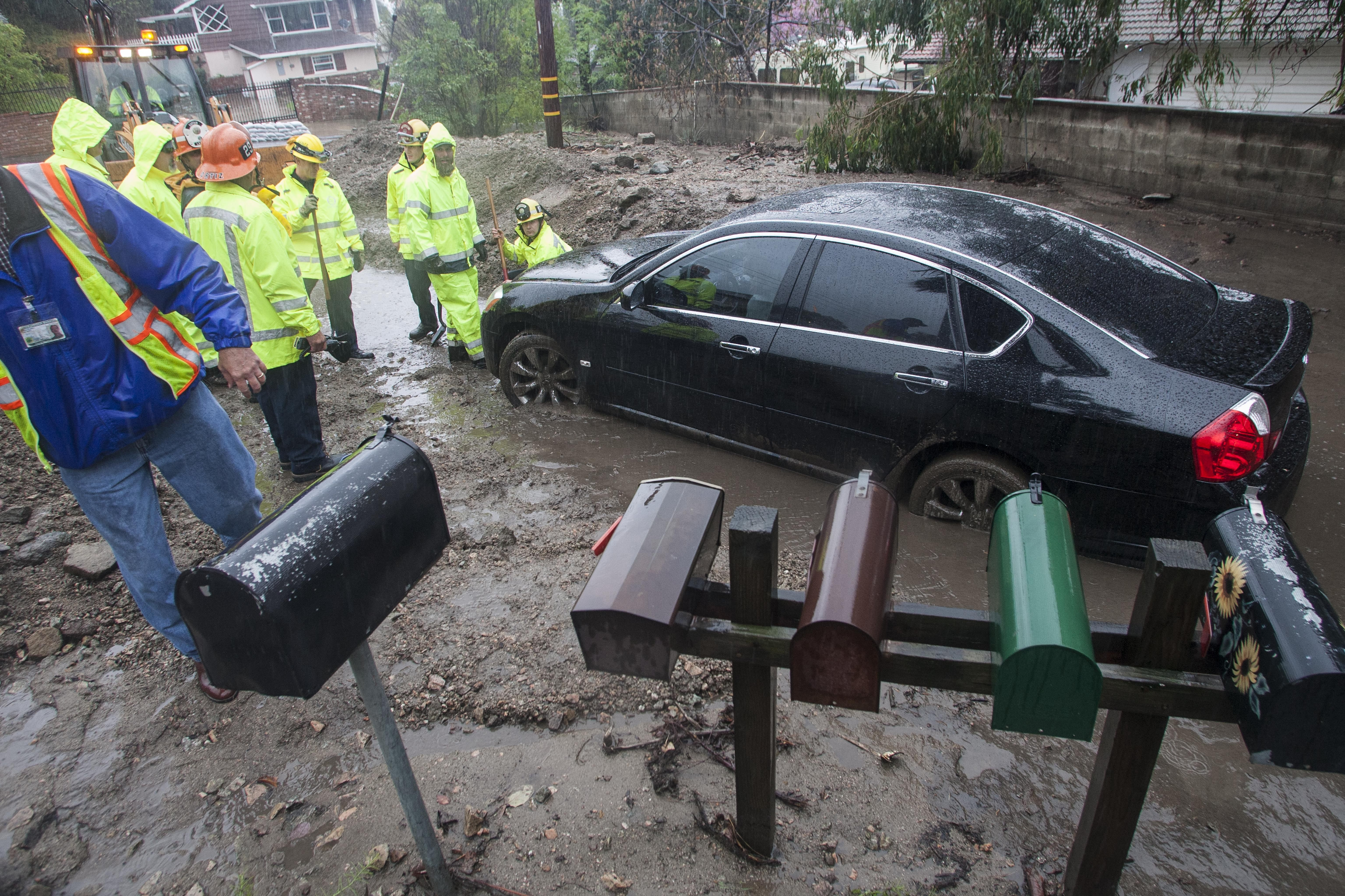 This car was stuck in mud up to its axles Friday after a mudslide in Glendora, Calif. Critically needed rain has given the state some relief but some problems as well.