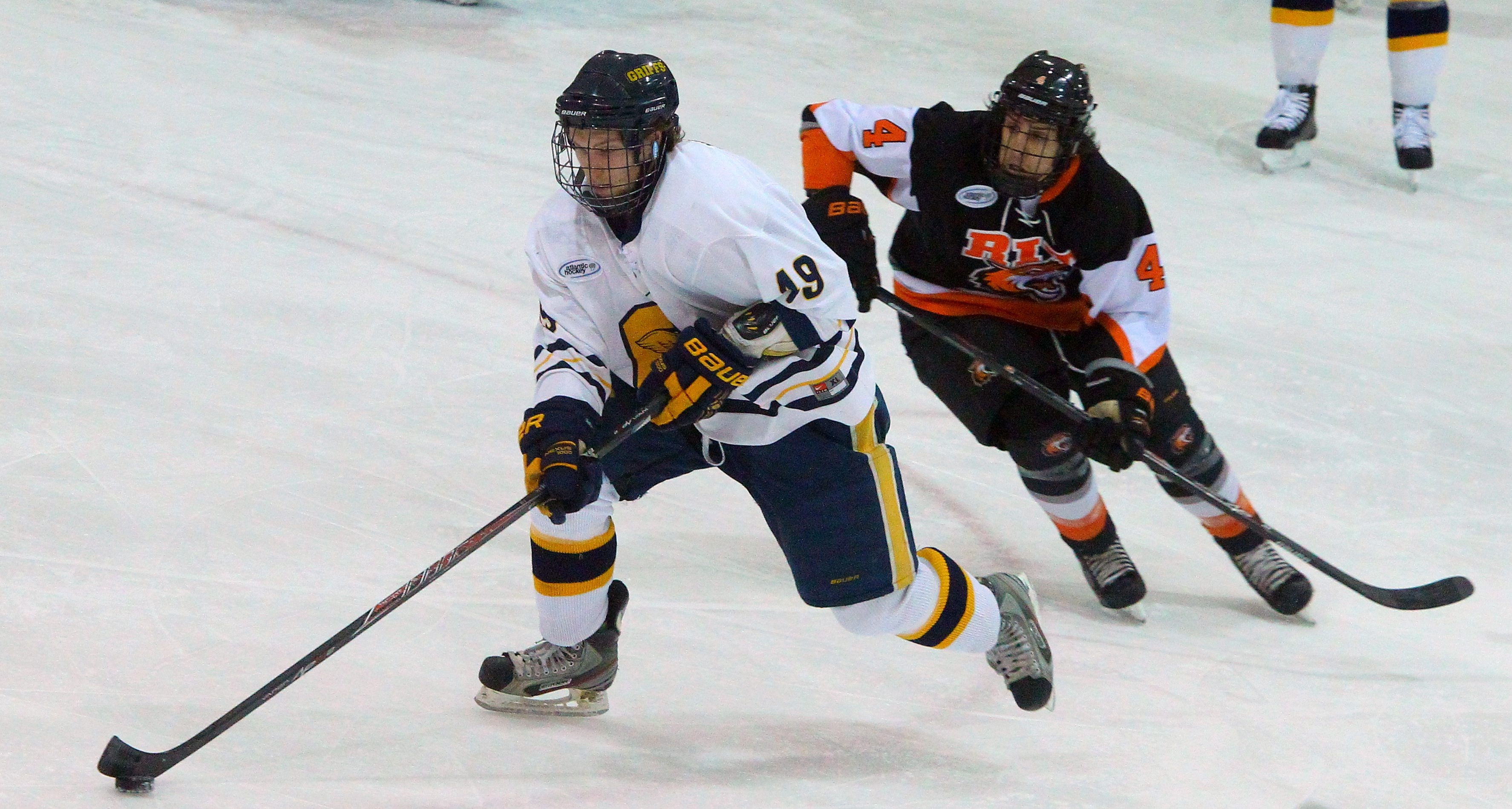 Tyler Wiseman of Canisius tries to clear the puck as RIT's Mike Colavecchia covers him in the first period at Buffalo State.
