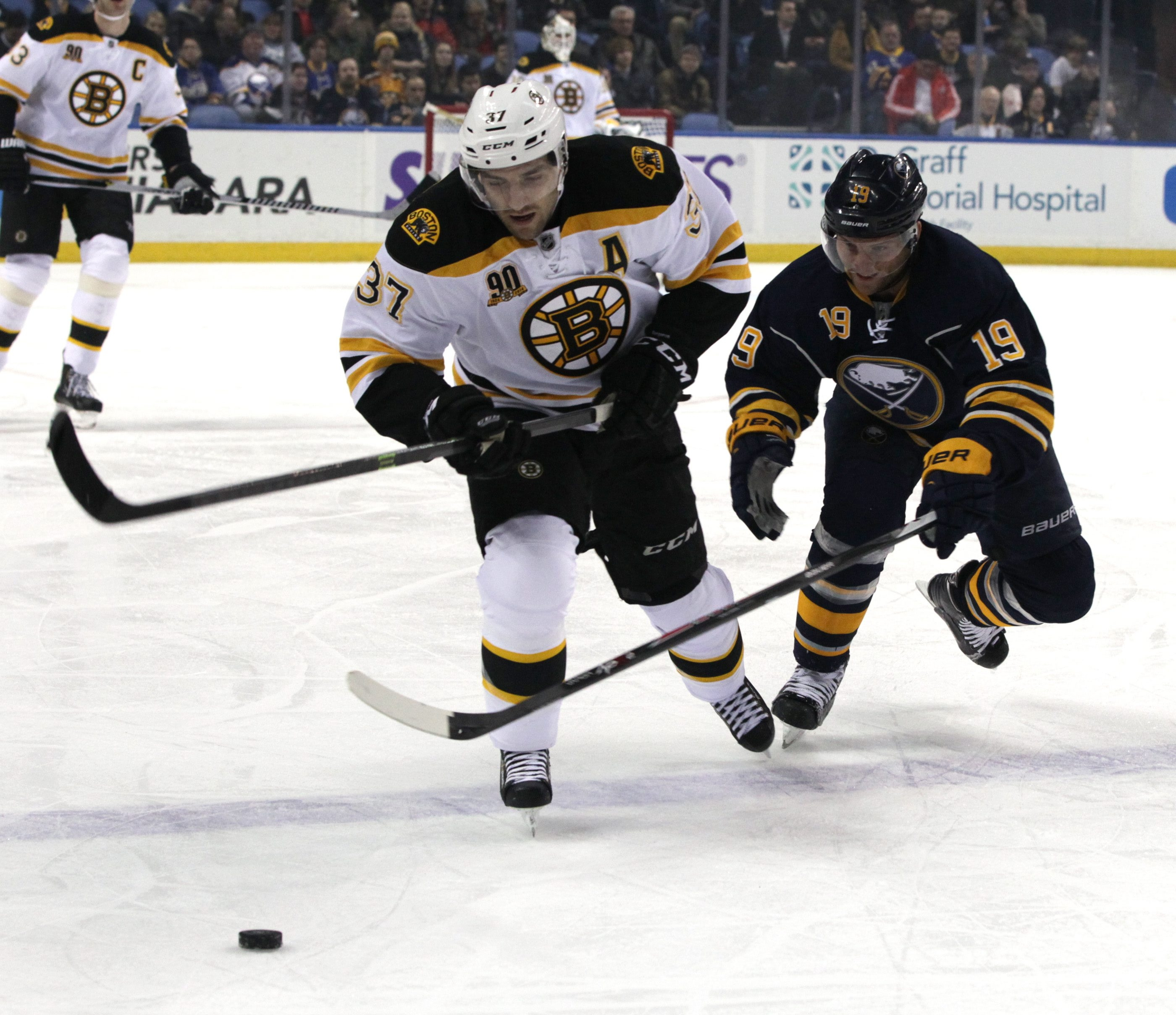 The Sabres' Cody Hodgson battles the Bruins' Patrice Bergeron for the puck in the first period.