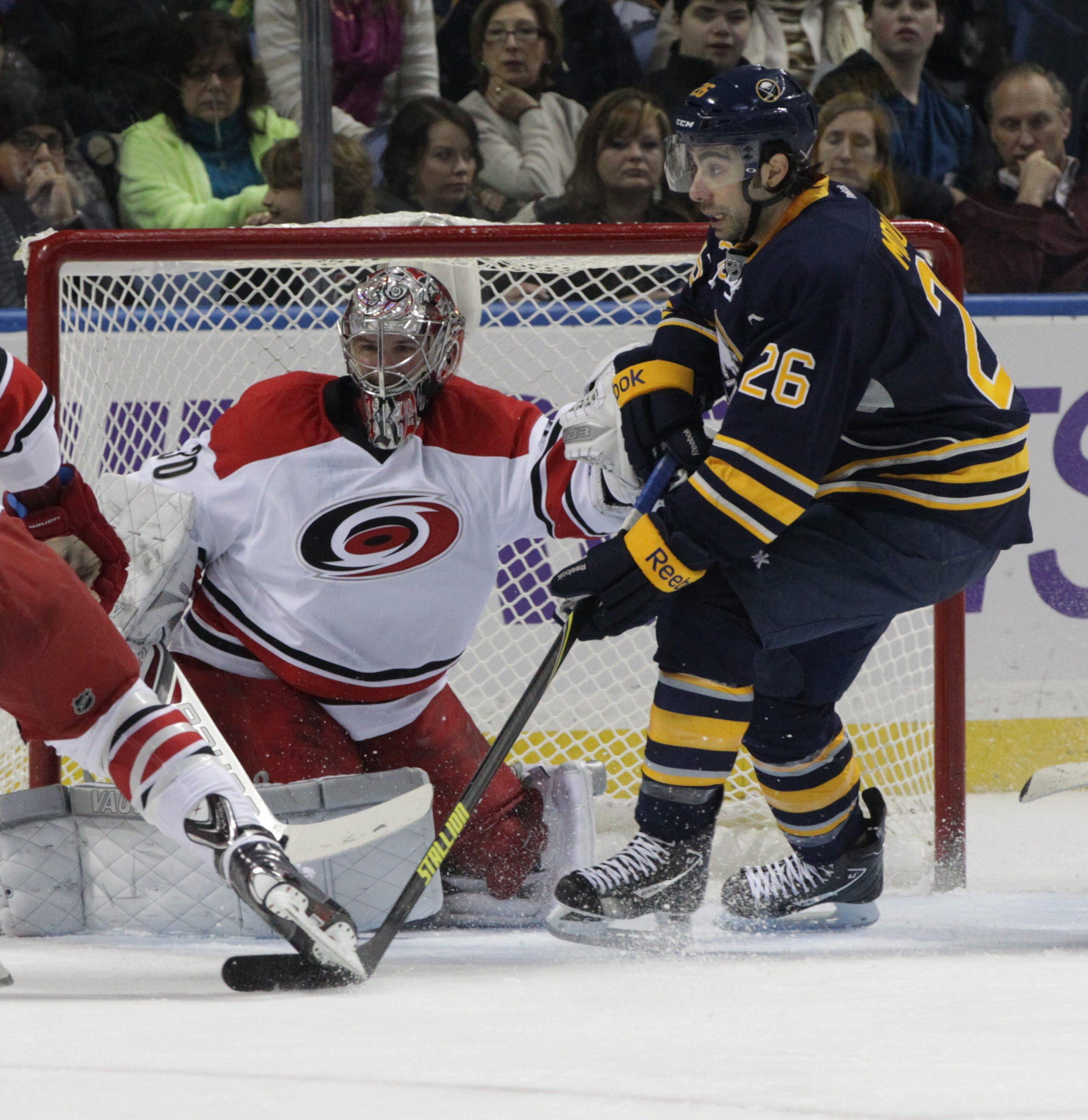 Buffalo's Matt Moulson (26) looks for the puck in front of Carolina goaltender Cam Ward.