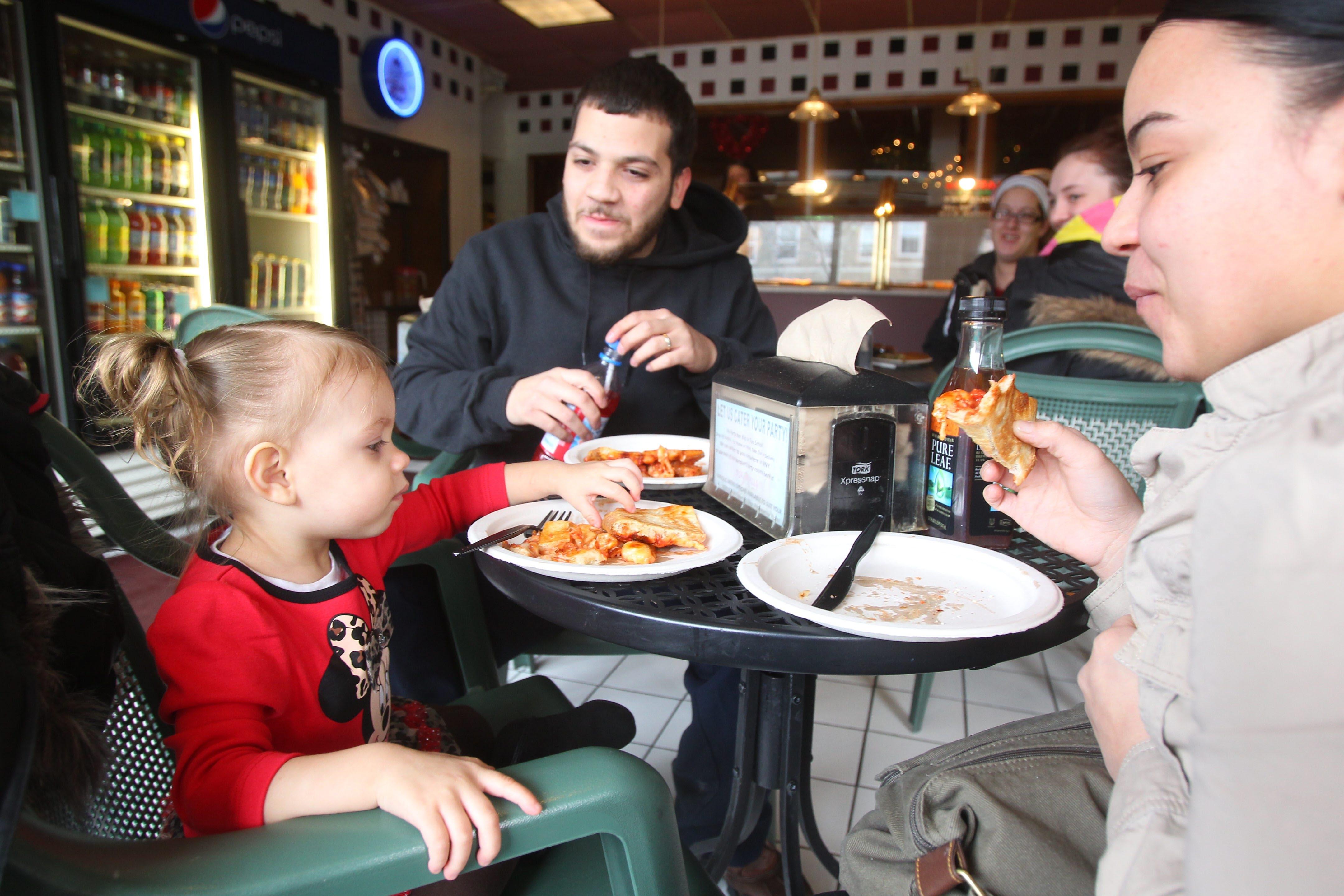 Janalyse Sanchez, left, enjoys a piece of pizza with her parents Venessa and Jorge at Casa-Di-Pizza.
