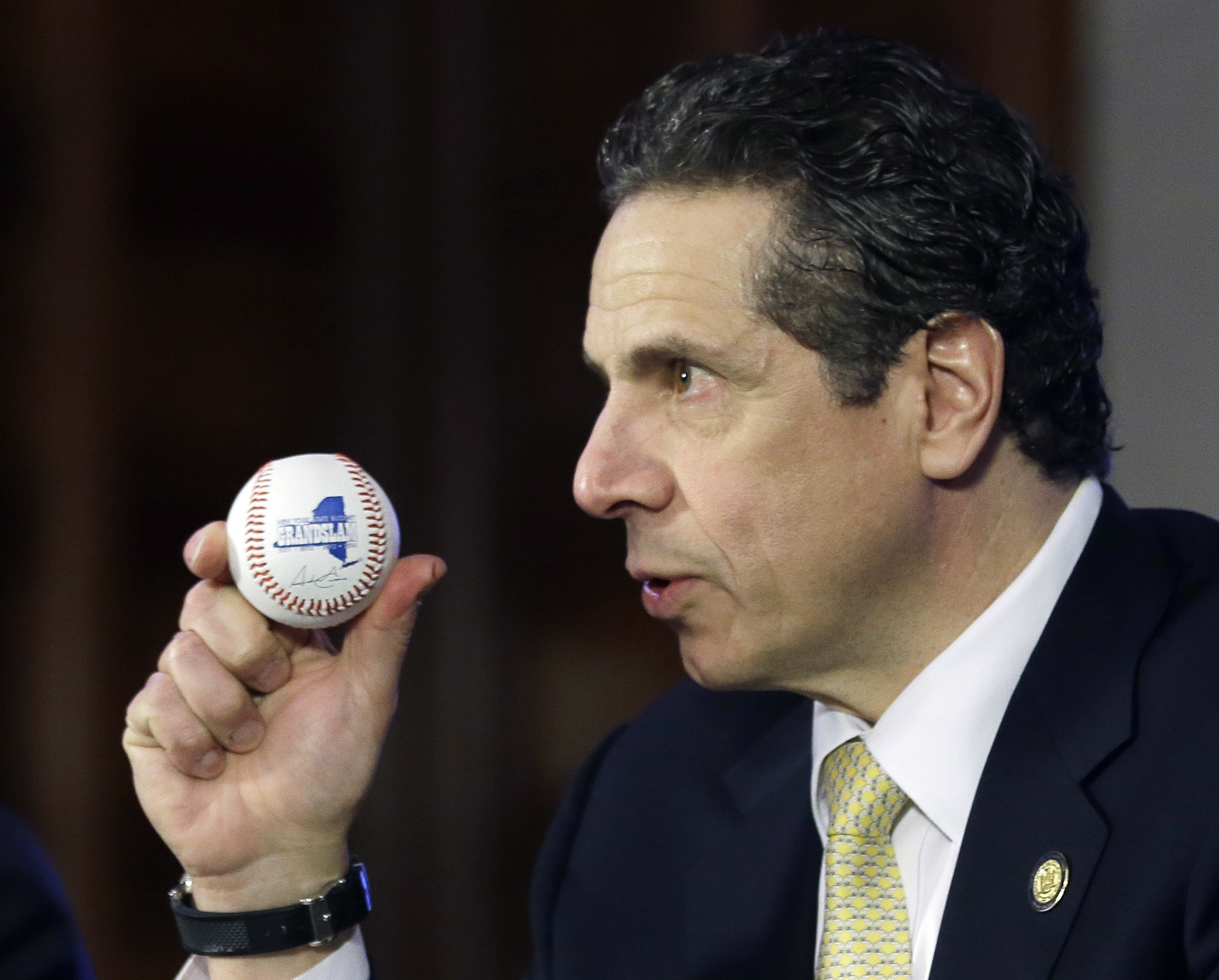 New York Gov. Andrew Cuomo holds a baseball as he speaks during a news conference and budget bill signing ceremony in the Red Room at the Capitol today. The New York Legislature on Monday passed a $140 billion election-year budget that will expand pre-kindergarten statewide and provide tax relief to homeowners and corporations. (AP Photo/Mike Groll)