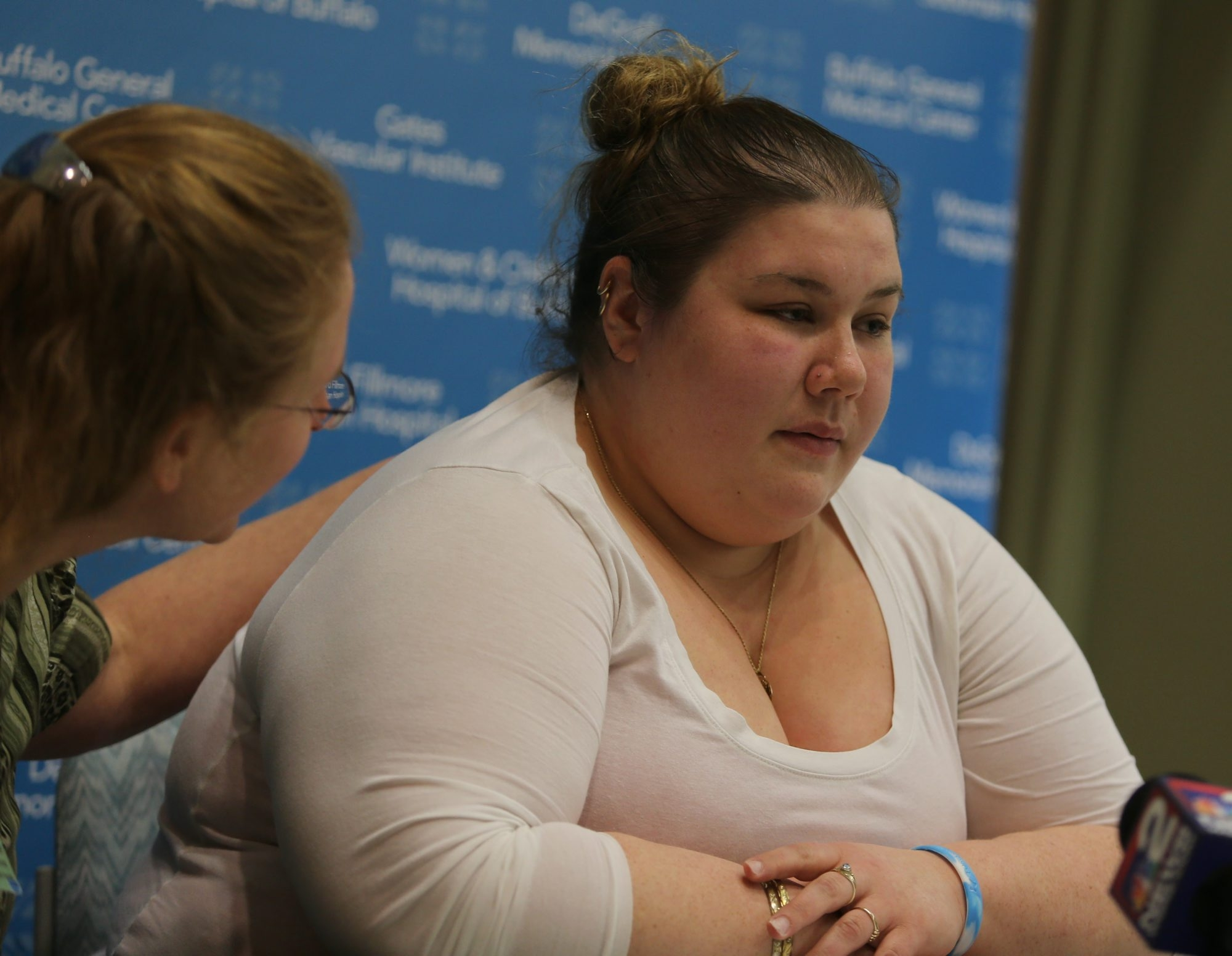 Amanda Castile, right, is comforted by Gail Bowden of UNYTS, left, as she speaks to the media Monday.
