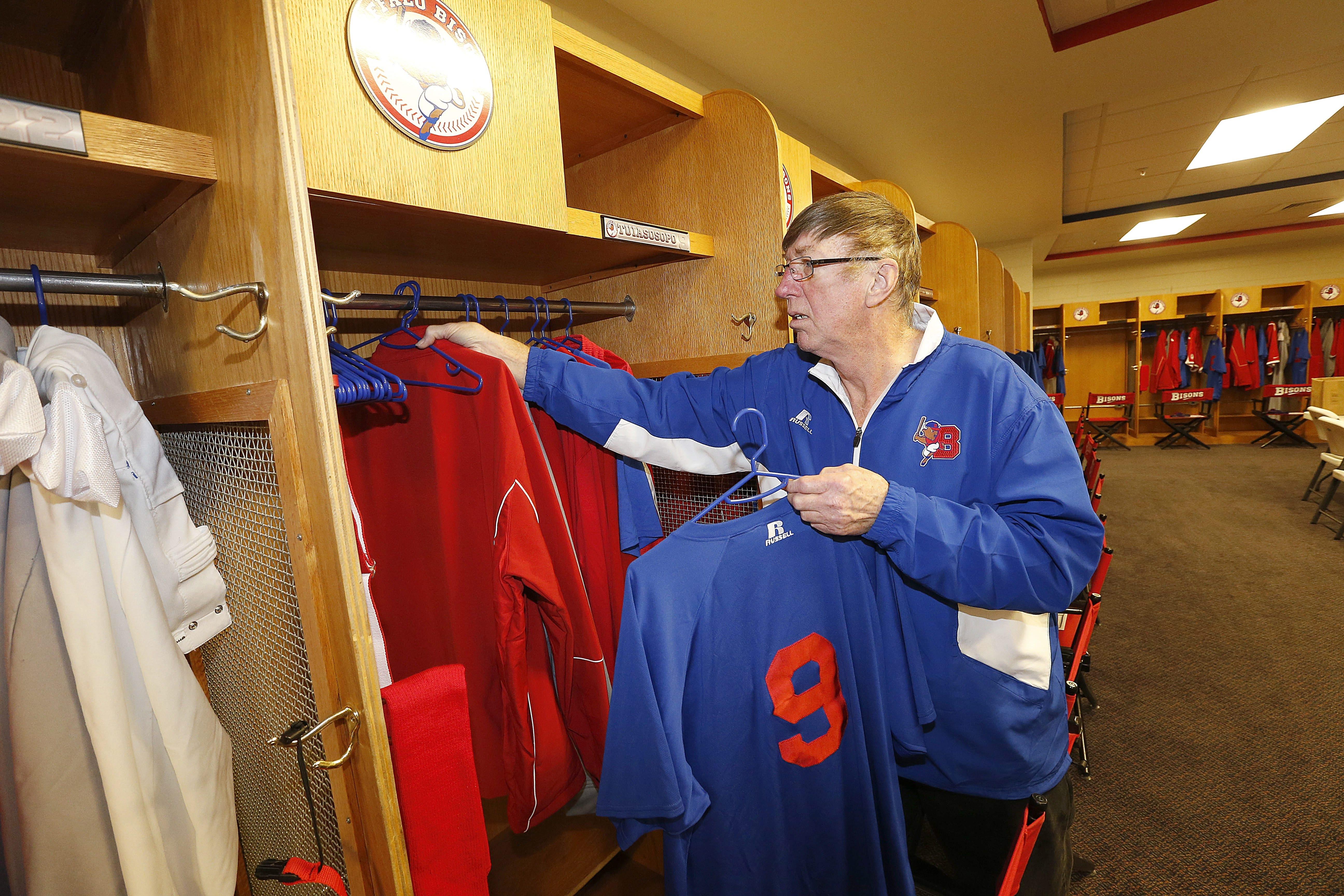 Club house assistant Bob Decker hangs up a Buffalo Bison uniform for Matt Tuiasospo in his locker at Coca-Cola Field.