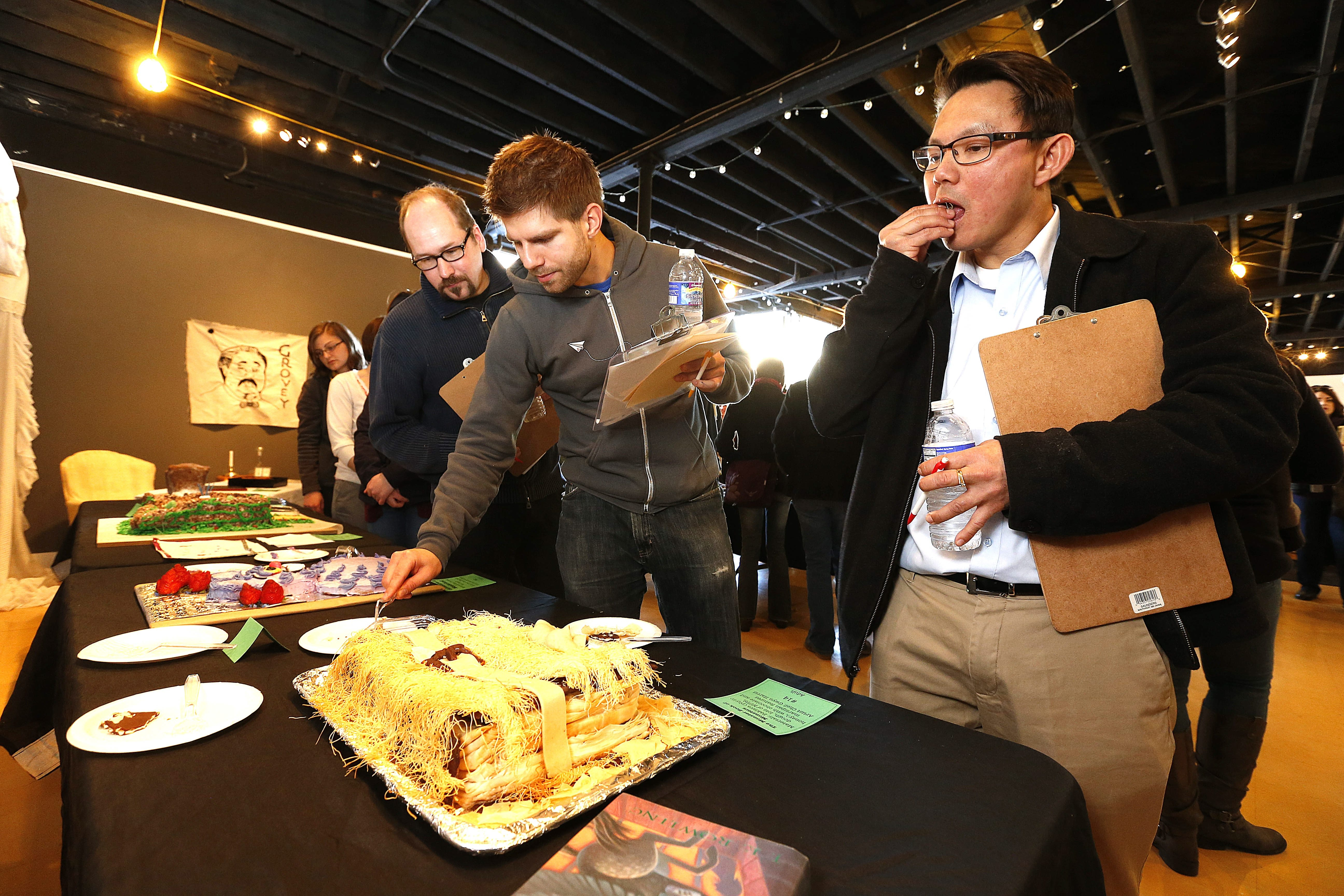 From left, Richard Kegler, Alex Levine and Kevin Lin, judge the entries at the Edible Books day at Western New York Book Arts Center on Sunday, March 30, 2014.