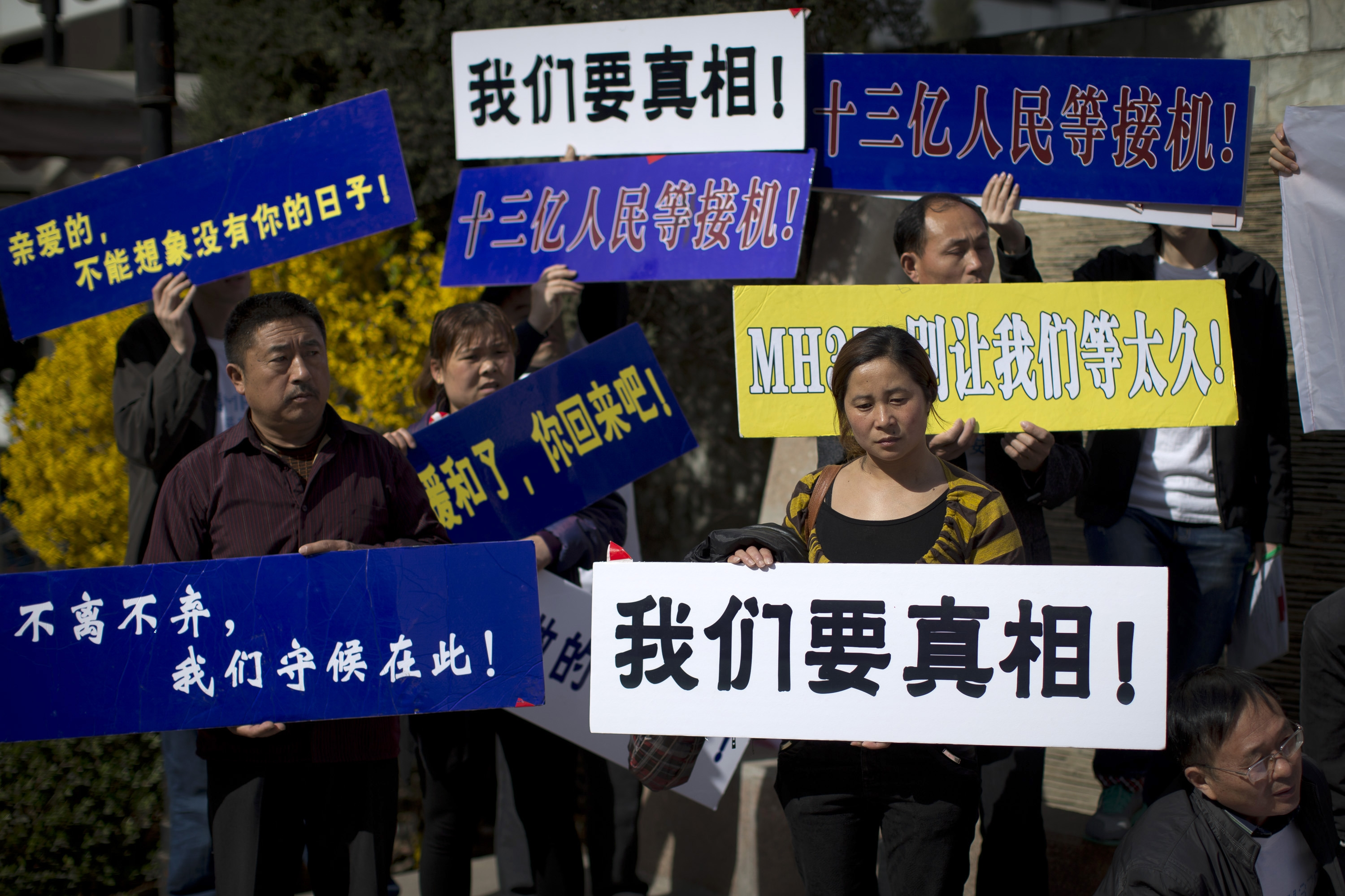 Relatives of Chinese passengers on Malaysia Airlines Flight 370 stage a protest against the airlines and the Malaysian government at a hotel in Beijing Saturday.