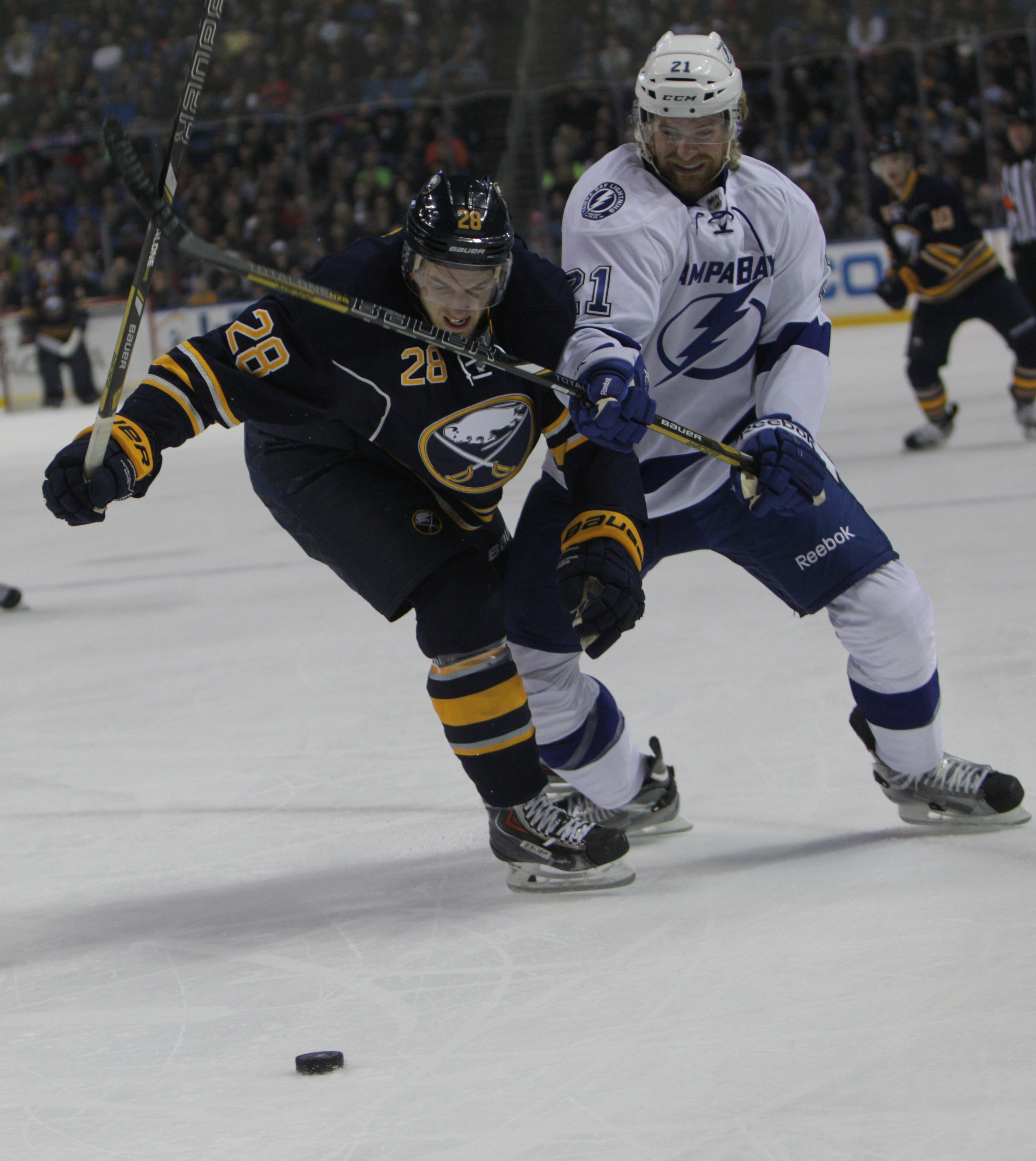 The Sabres' Zemgus Girgensons fights for the puck with Tampa Bay's Michael Kostka as Girgensons returned to the lineup after missing 11 games.